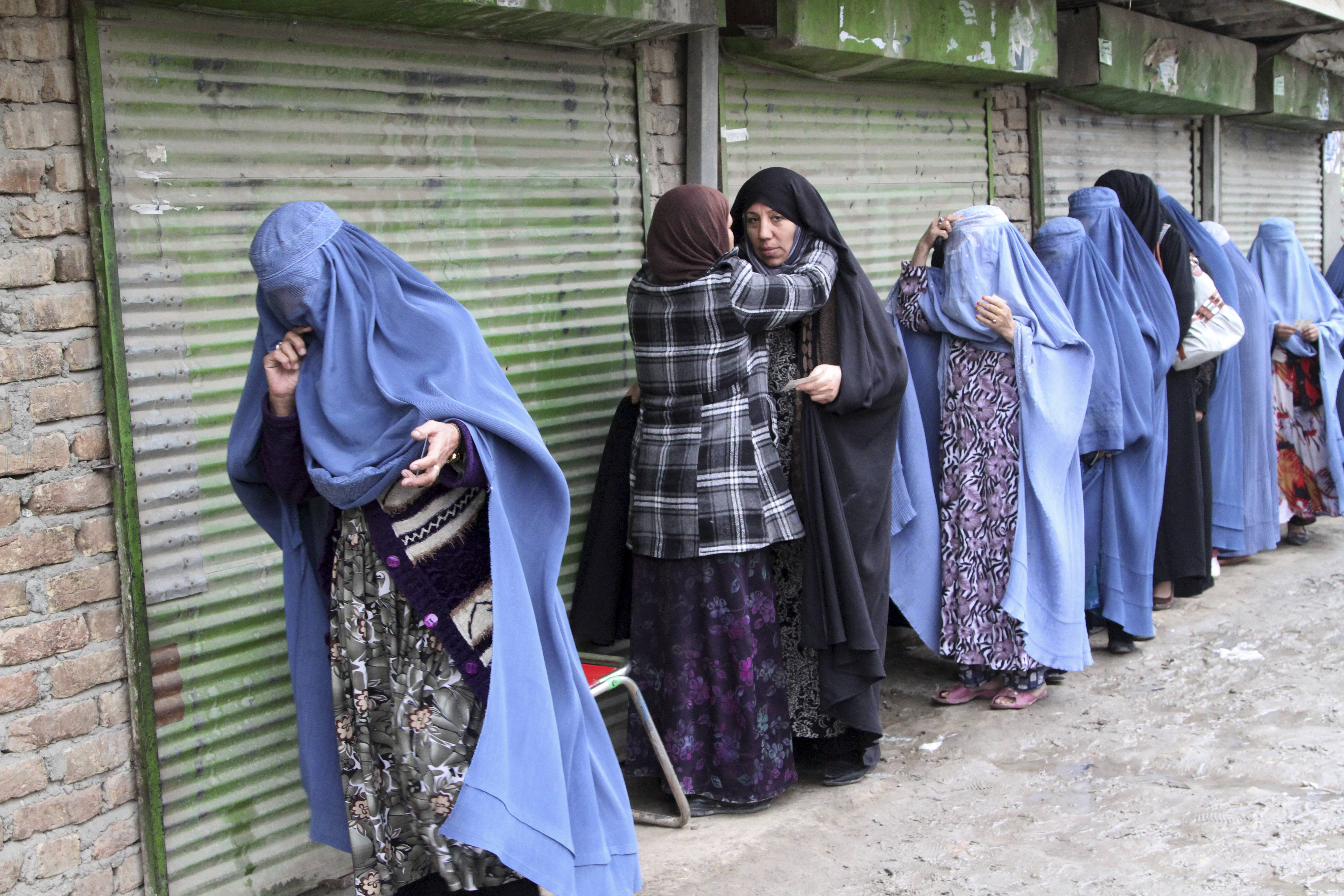 An Afghan woman searches voters before they enter a polling station to cast their ballots, in Kabul, Afghanistan, Saturday.