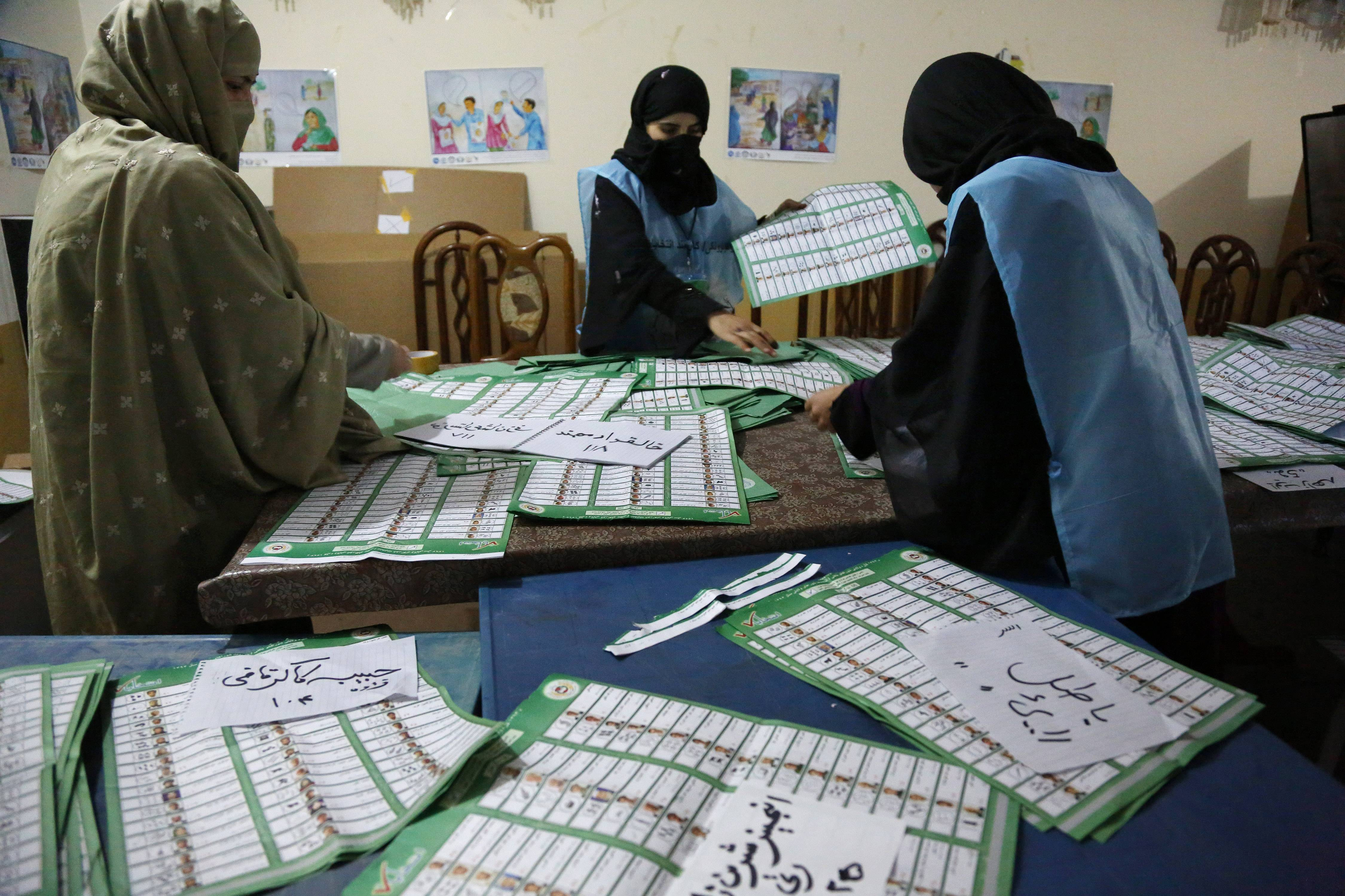 Afghan election workers counts ballots at a polling station in Jalalabad, east of Kabul, Afghanistan, Saturday.