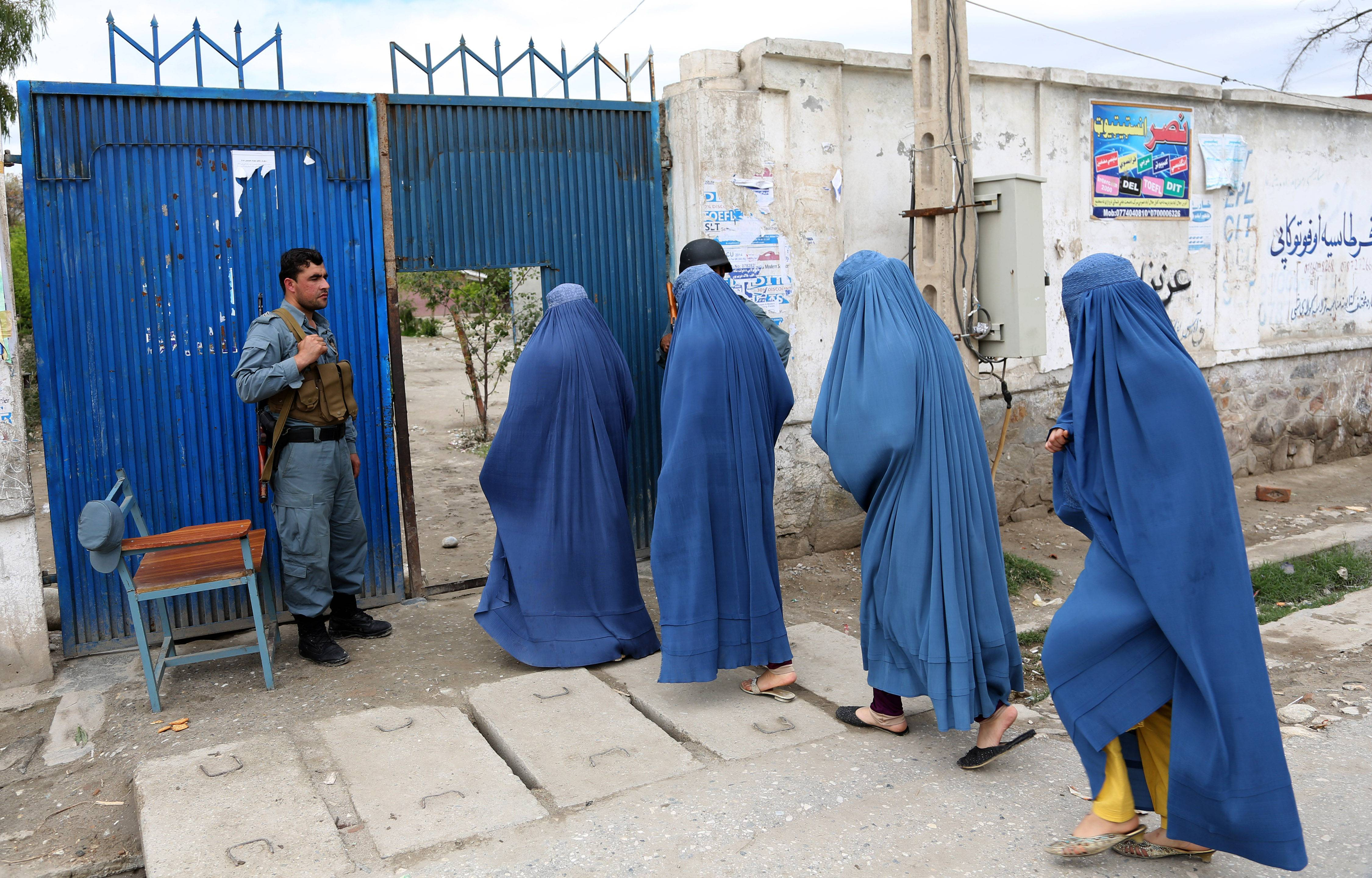 Afghan women enter a polling station to vote in Jalalabad, east of Kabul, Afghanistan, Saturday.