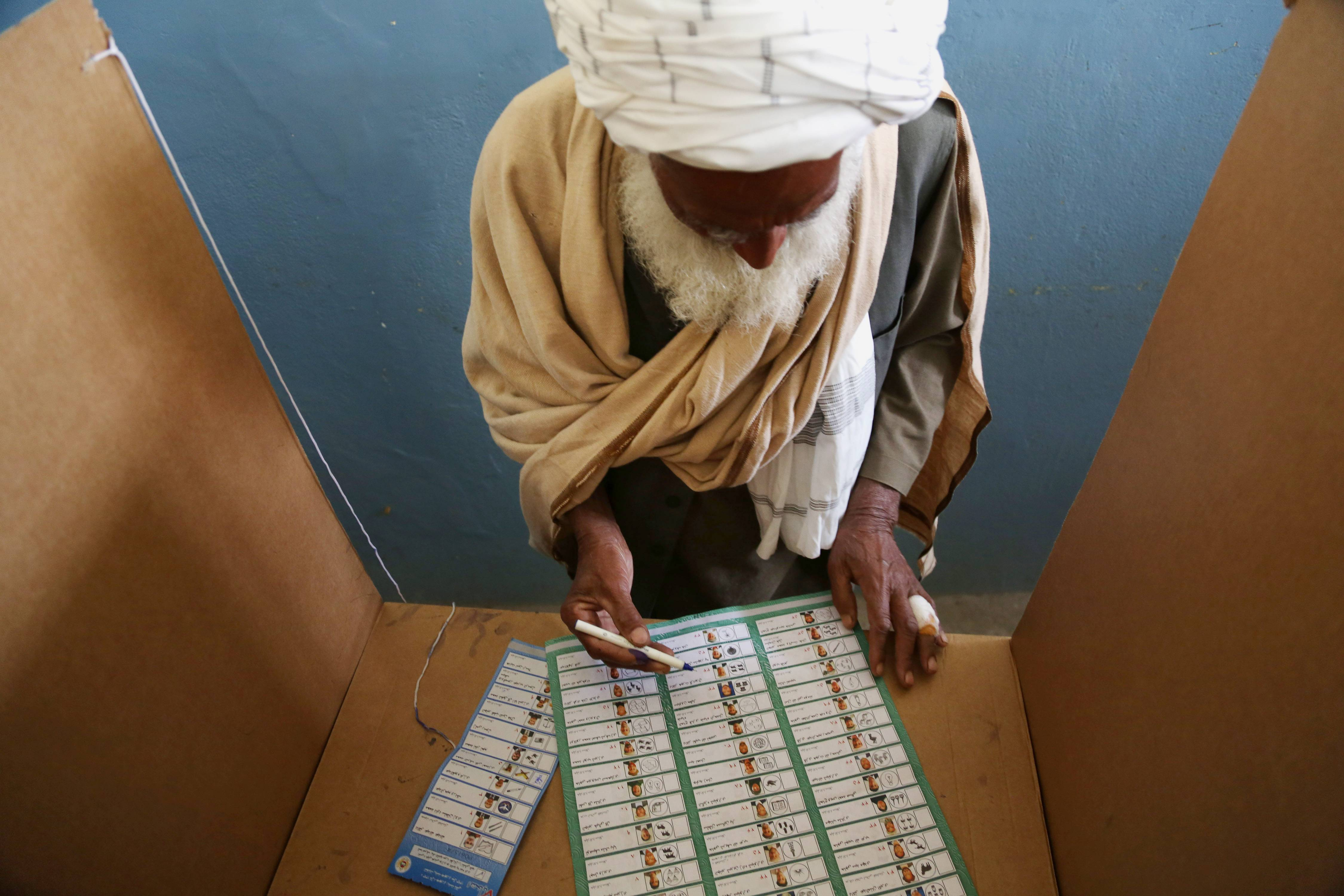 An Afghan man fills his ballot at a polling station in Jalalabad, east of Kabul, Afghanistan, Saturday.