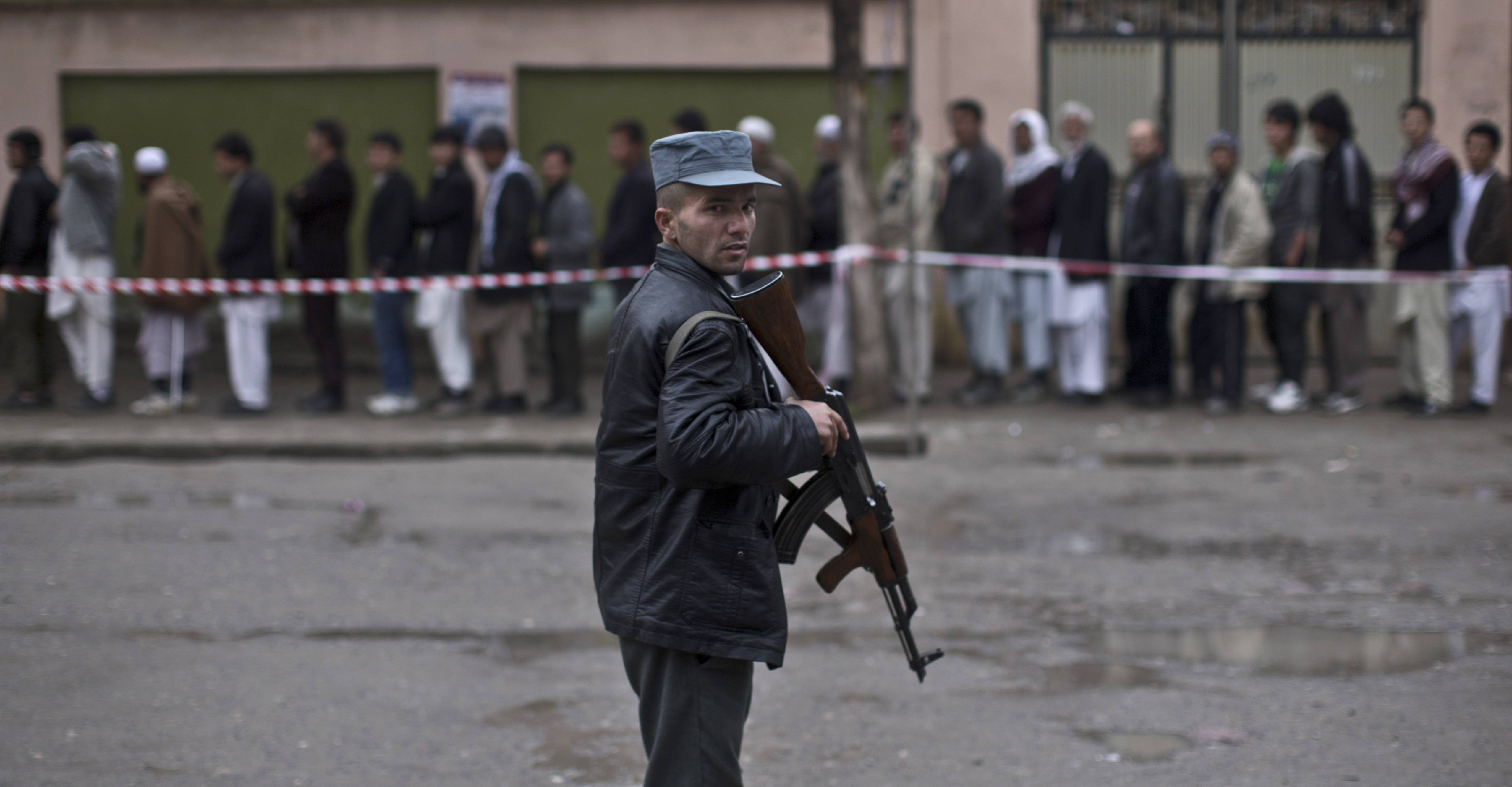 An Afghan policeman stands guard while voters line up to enter a polling station and cast their ballots in Kabul, Afghanistan, Saturday.