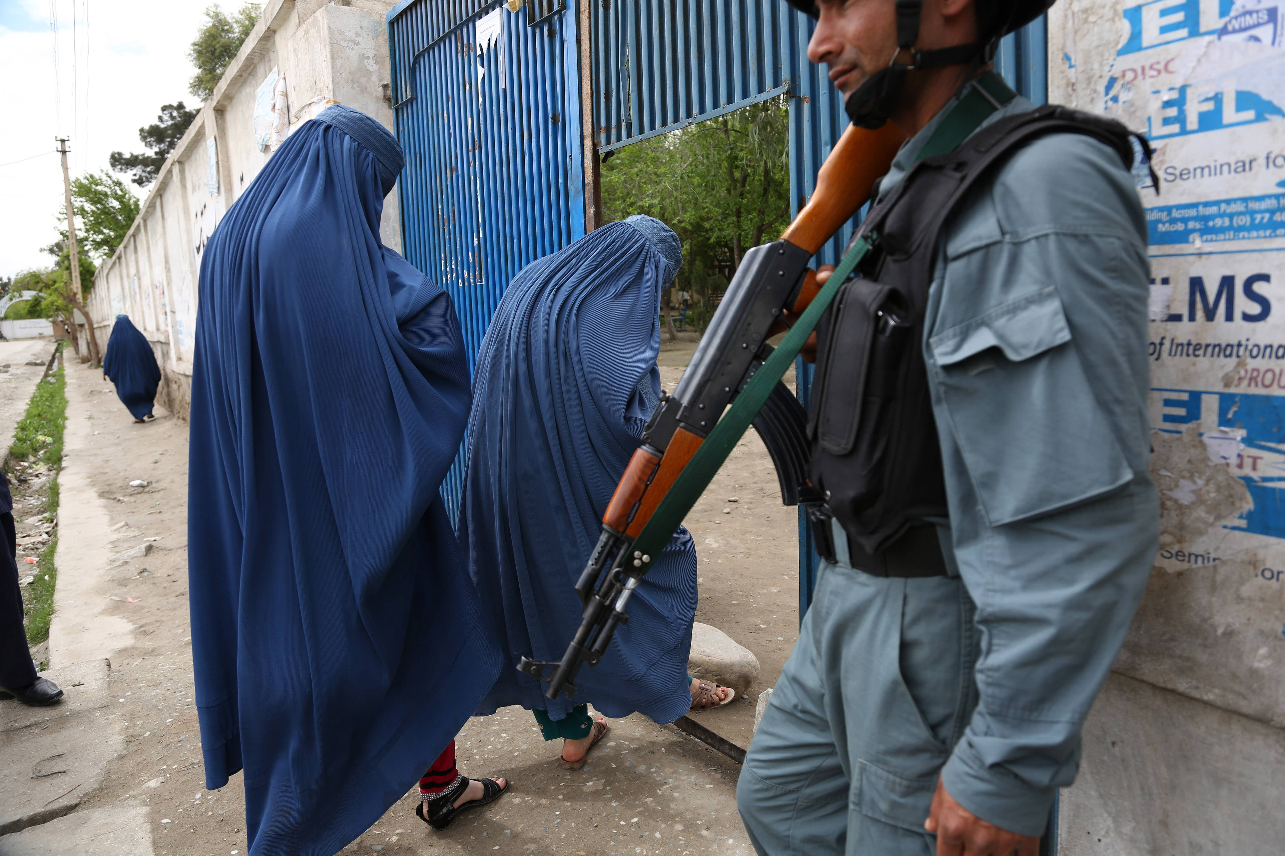 An Afghan policeman stands guard at a gate to a polling station in Jalalabad, east of Kabul, Afghanistan, Saturday.