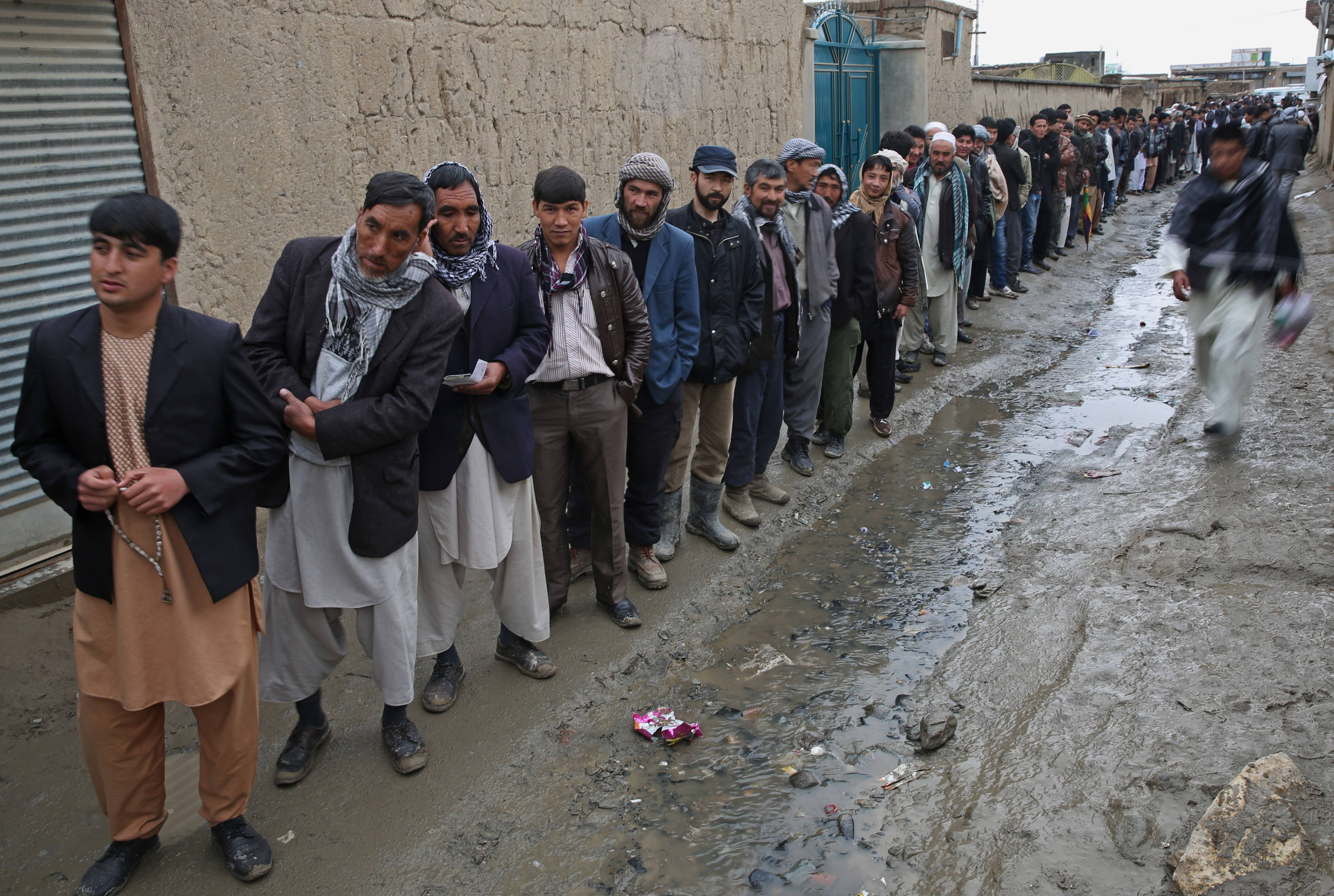 Afghan men line up for the registration process before they cast their votes at a polling station in Kabul, Afghanistan, Saturday.