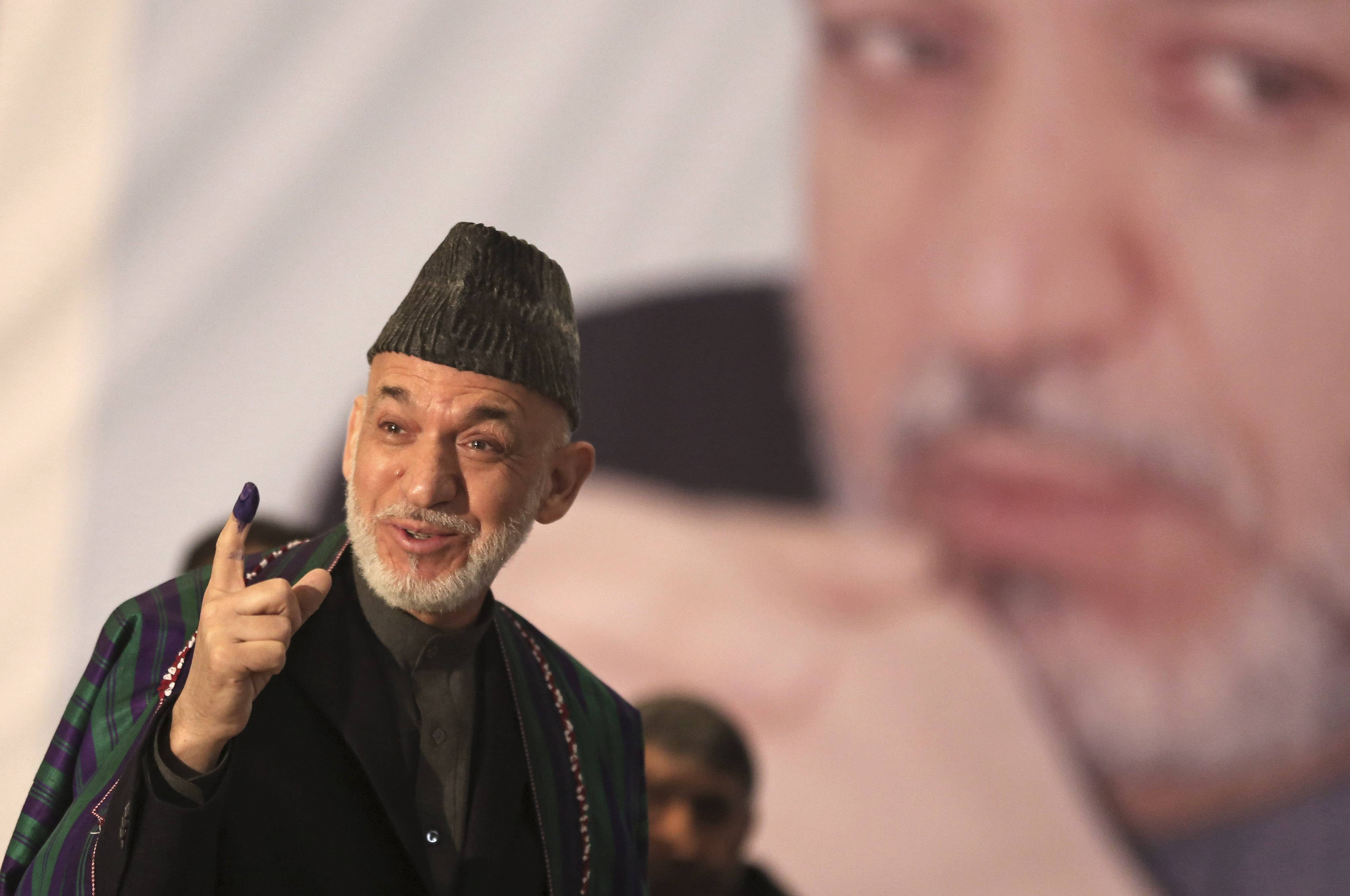 Afghan President Hamid Karzai shows indelible ink on his finger to the media before he casts his vote at Amani High School, near the presidential palace in Kabul, Afghanistan, Saturday.