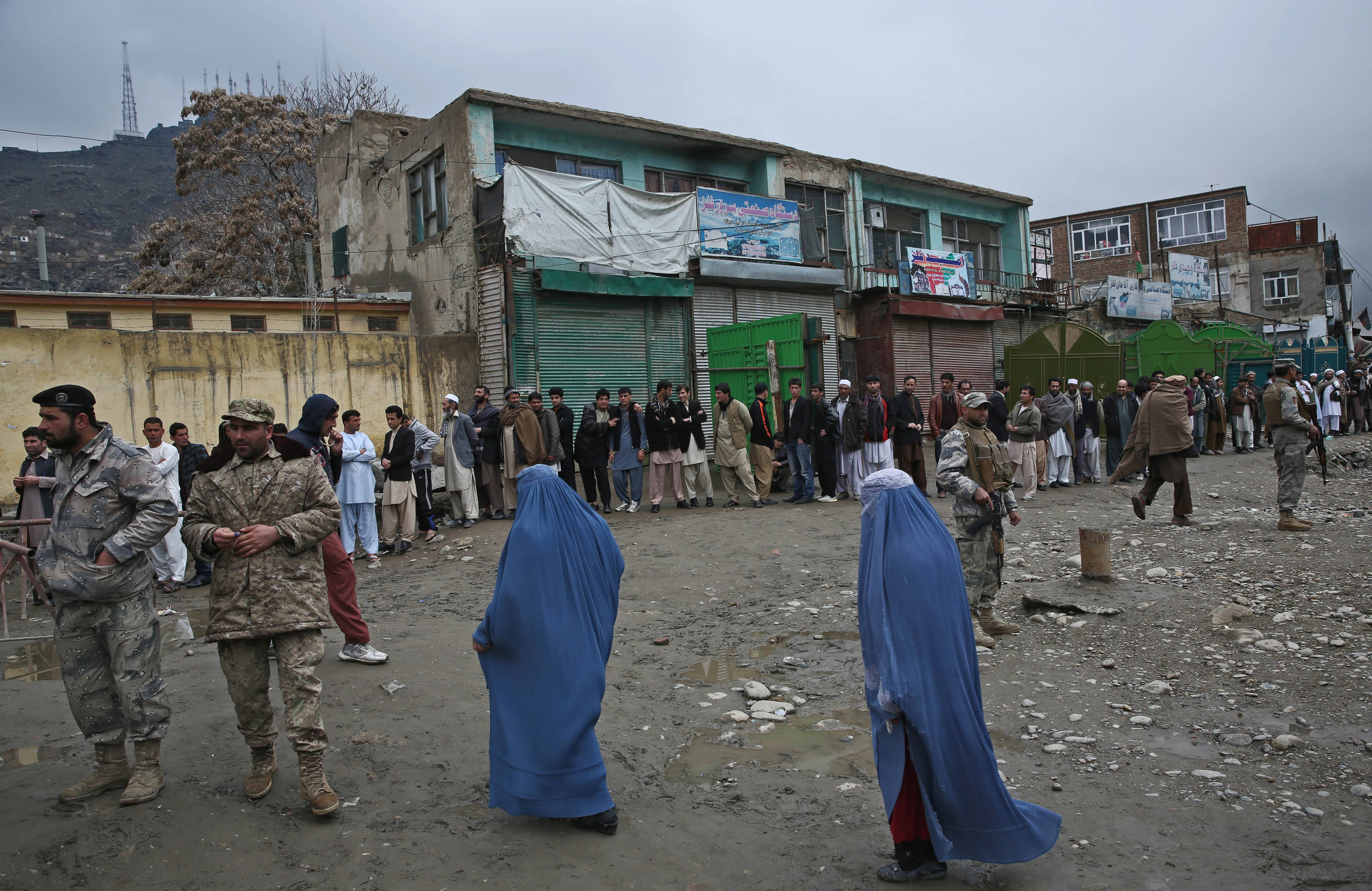 Afghan men line up for registration process before they cast their votes outside a polling station as burqa-clad women walk past the polling station in Kabul, Afghanistan, Saturday.