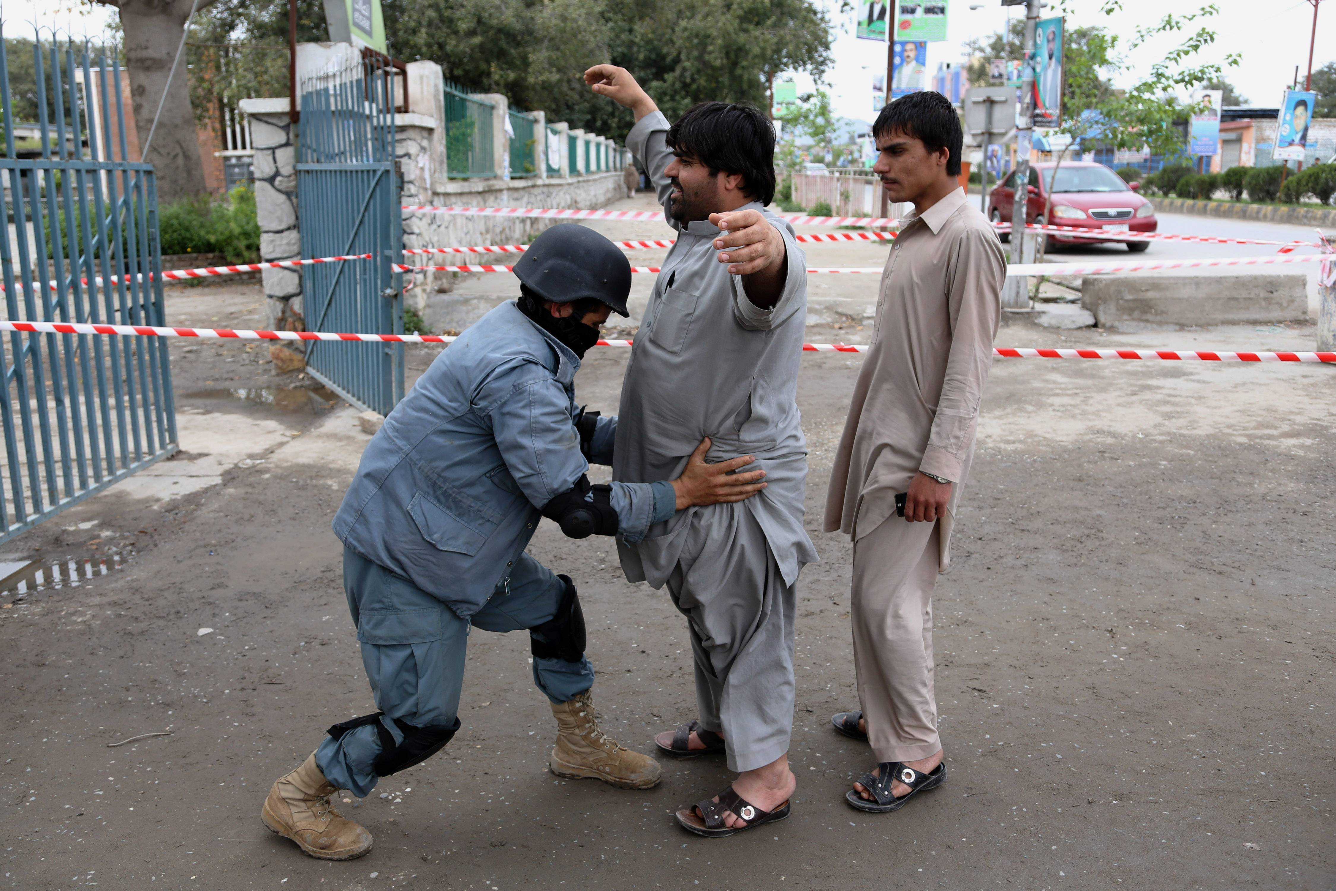 An Afghan policeman frisks a man at a polling station in Jalalabad, east of Kabul, Afghanistan, Saturday.