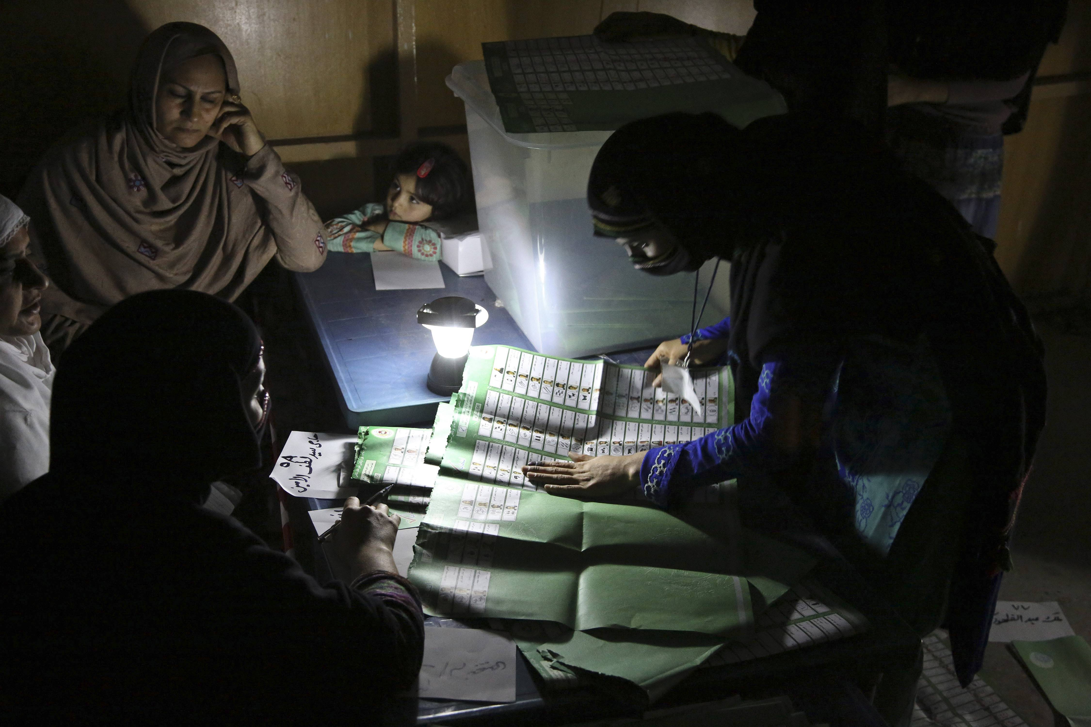 Afghan election workers count ballots by the light of a lantern at a polling station in Jalalabad, east of Kabul, Afghanistan, Saturday.