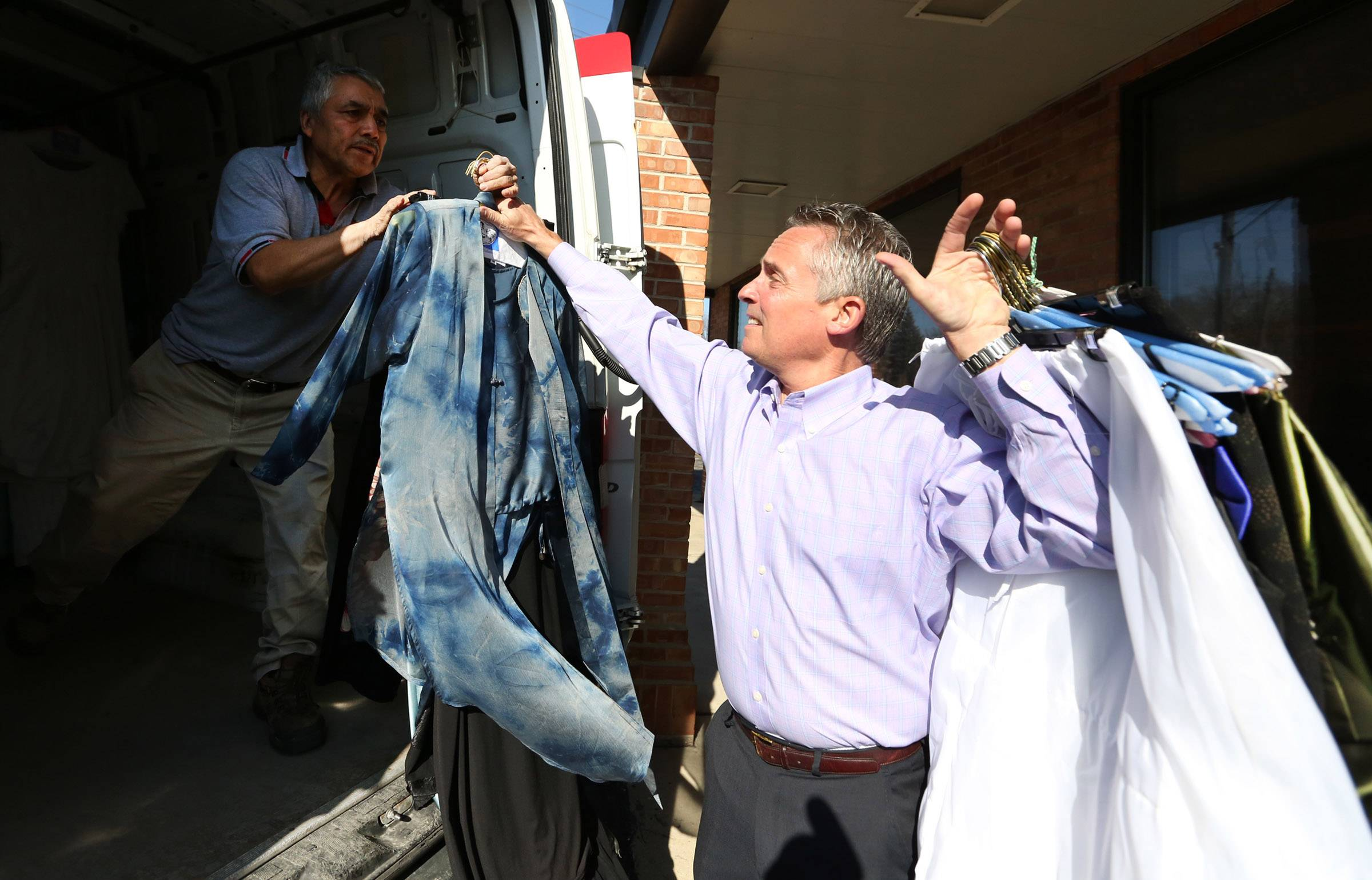 Tom Zengeler, owner of Zengeler Cleaners, hands donated prom dresses to Enrique Tovar in a van at the cleaners in Northbrook on Saturday. The dresses are being delivered to Chicago for girls from needy families as part of the Glass Slipper Project.