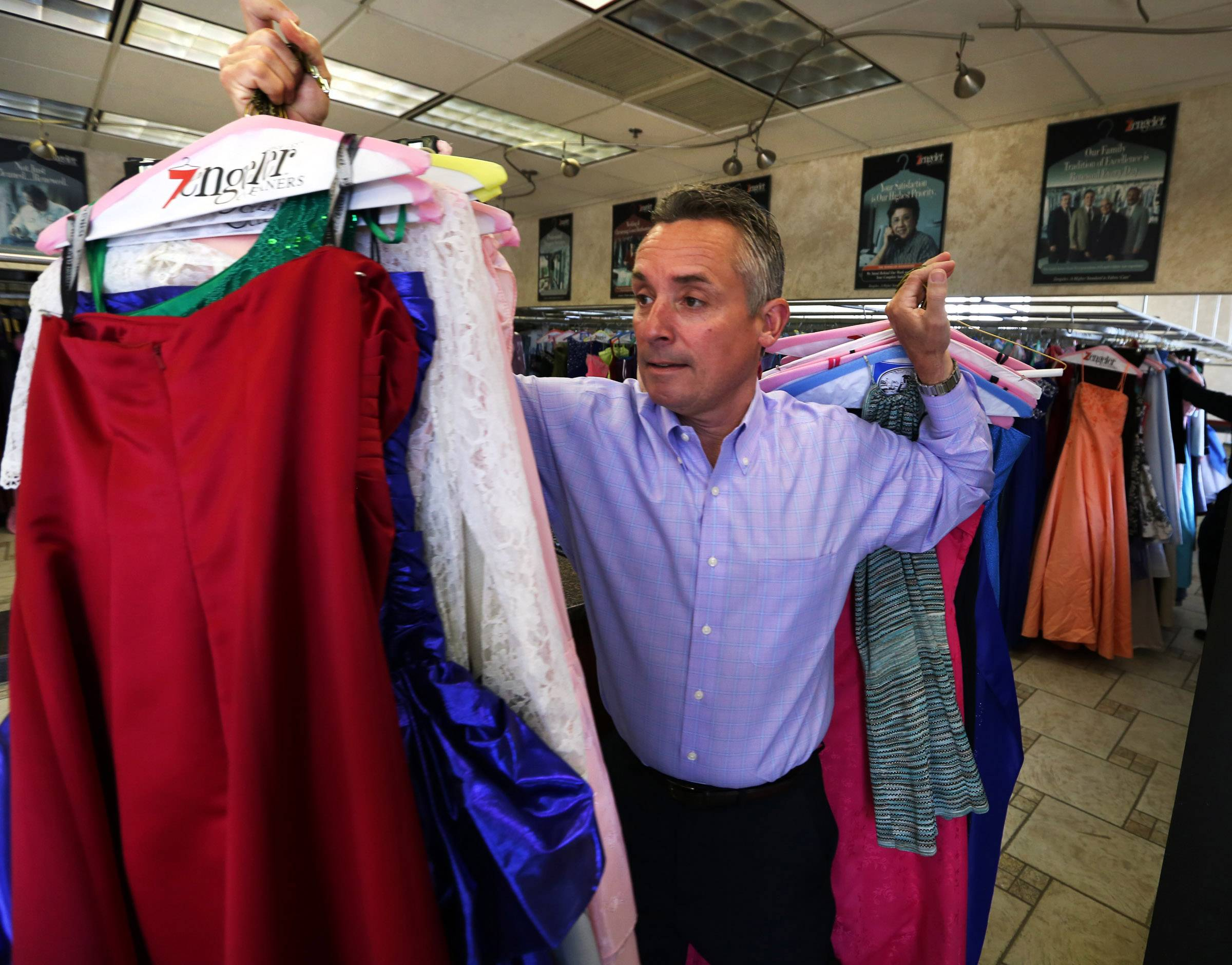 Tom Zengeler, owner of Zengeler Cleaners, carries prom dresses out of cleaners in Northbrook to a van on Saturday. The dresses are being delivered to Chicago for girls from needy families as part of the Glass Slipper Project.