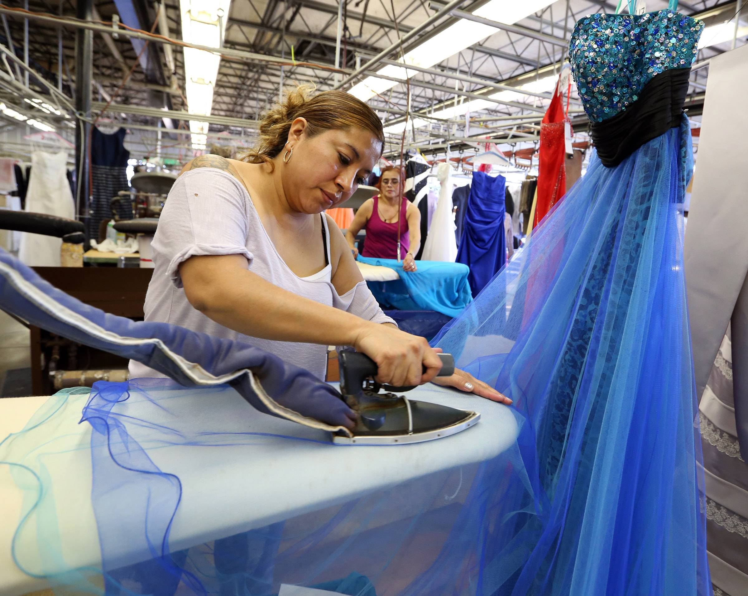 Maria Marroquin steam irons prom dresses at Zengeler Cleaners with Antonia Chavez, background right, ironing other dresses on Saturday in Northbrook. The dresses are being delivered to Chicago for girls from needy families as part of the Glass Slipper Project.