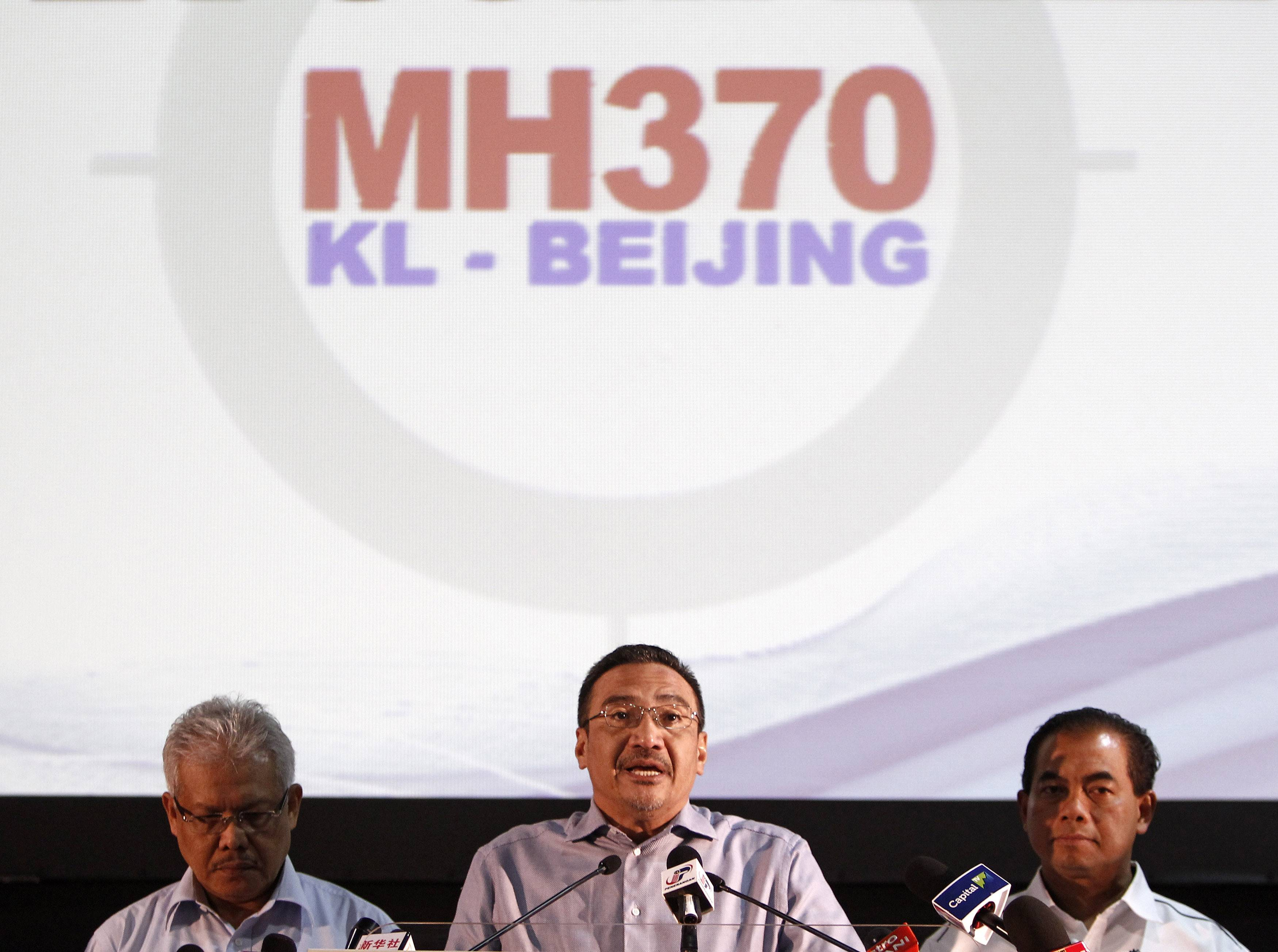 Malaysian acting Transport Minister Hishammuddin Hussein, center, speaks as Malaysian Deputy Foreign Minister Hamzah Zainuddin, left, and Malaysian Deputy Transport Minister Abdul Aziz Kaprawi listen during a news conference for the missing Malaysia Airlines Flight MH370, in Kuala Lumpur, Malaysia, Saturday, April 5, 2014. Search teams racing against time to find the flight recorders from the missing Malaysia Airlines jet crisscrossed another patch of the Indian Ocean on Saturday, four weeks to the day after the airliner vanished.