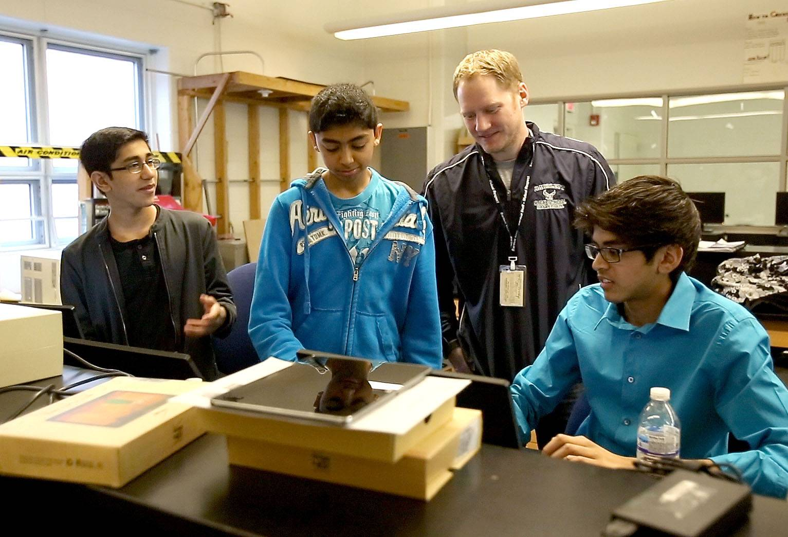 Bartlett teacher Phil Church, center, encourages students Purav Shah, left, Shil Shah and Amar Patel, right.