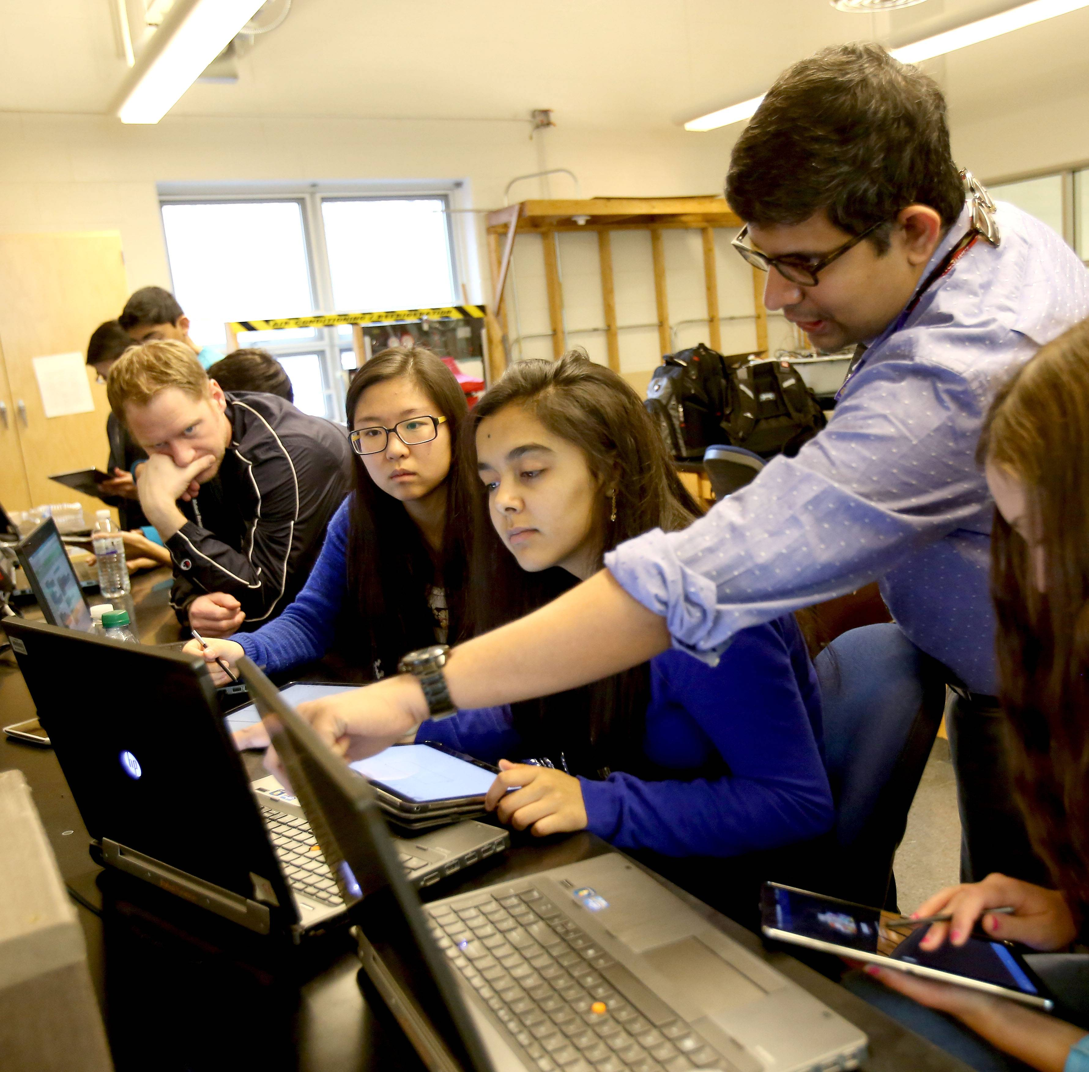 Krishnendu Roy helps Autumn Chung, left, and Aishwarya Jois, center, solve a programming hiccup.