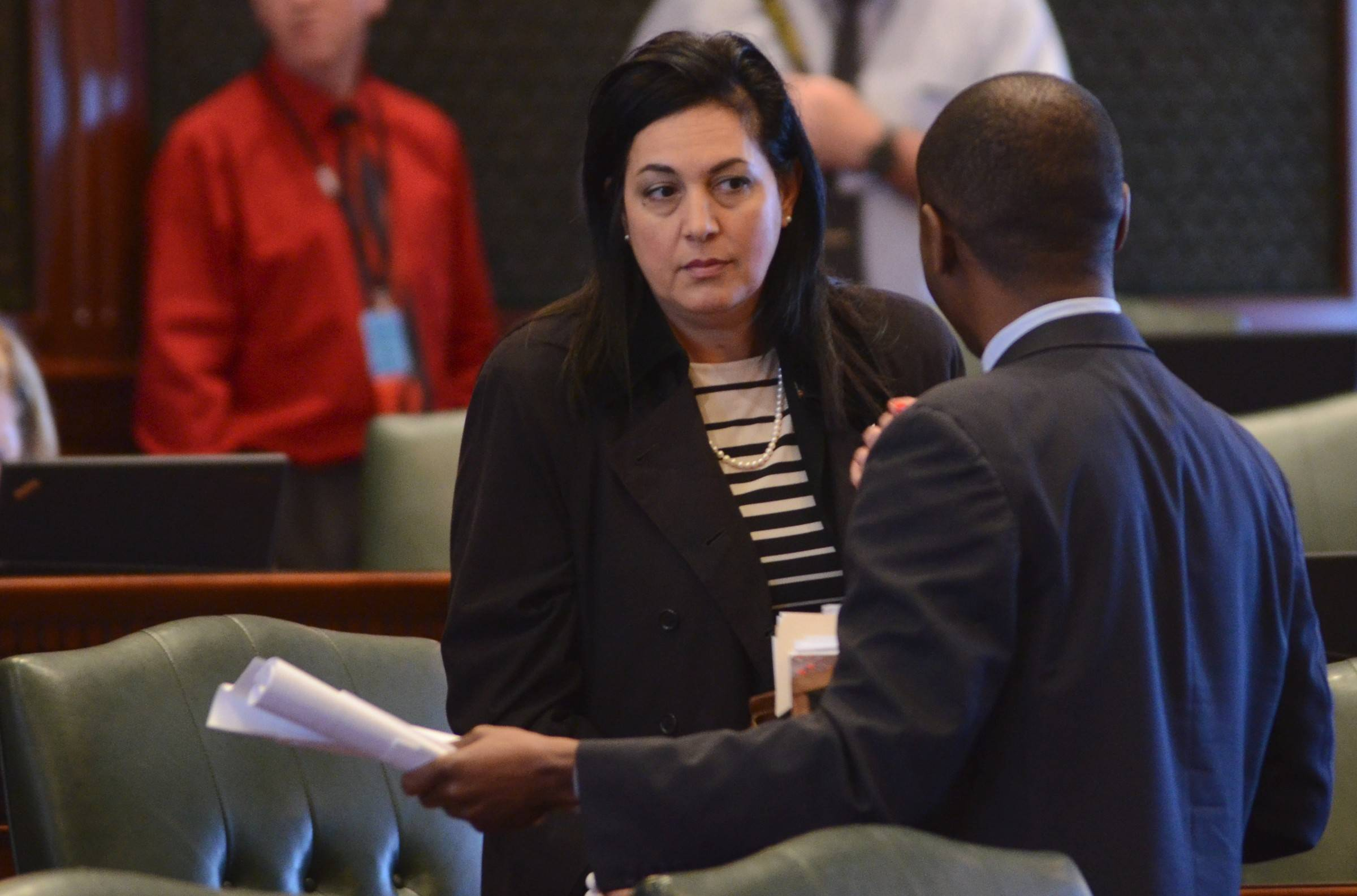 State Rep. Linda Chapa LaVia, an Aurora Democrat, speaks with state Rep. La Shawn Ford, a Chicago Democrat, on the Illinois House floor. Chapa LaVia says she isn't working toward a state takeover of the Illinois High School Association.