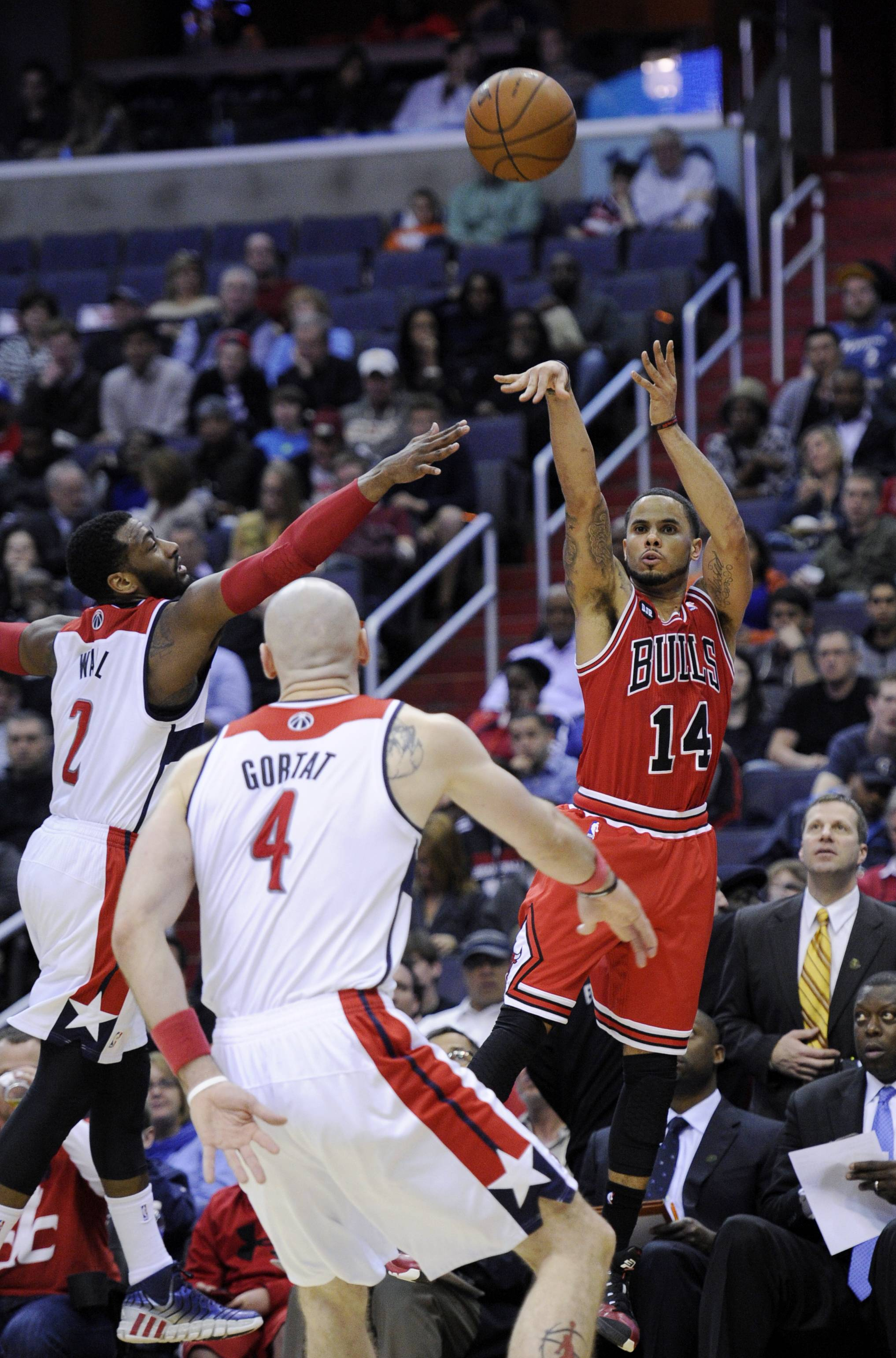 Bulls guard D.J. Augustin (14) takes a shot against Washington Wizards' John Wall (2) and Marcin Gortat (4), of Poland, during the first half of an NBA basketball game, Saturday, April 5, 2014, in Washington. The Bulls won 96-78.