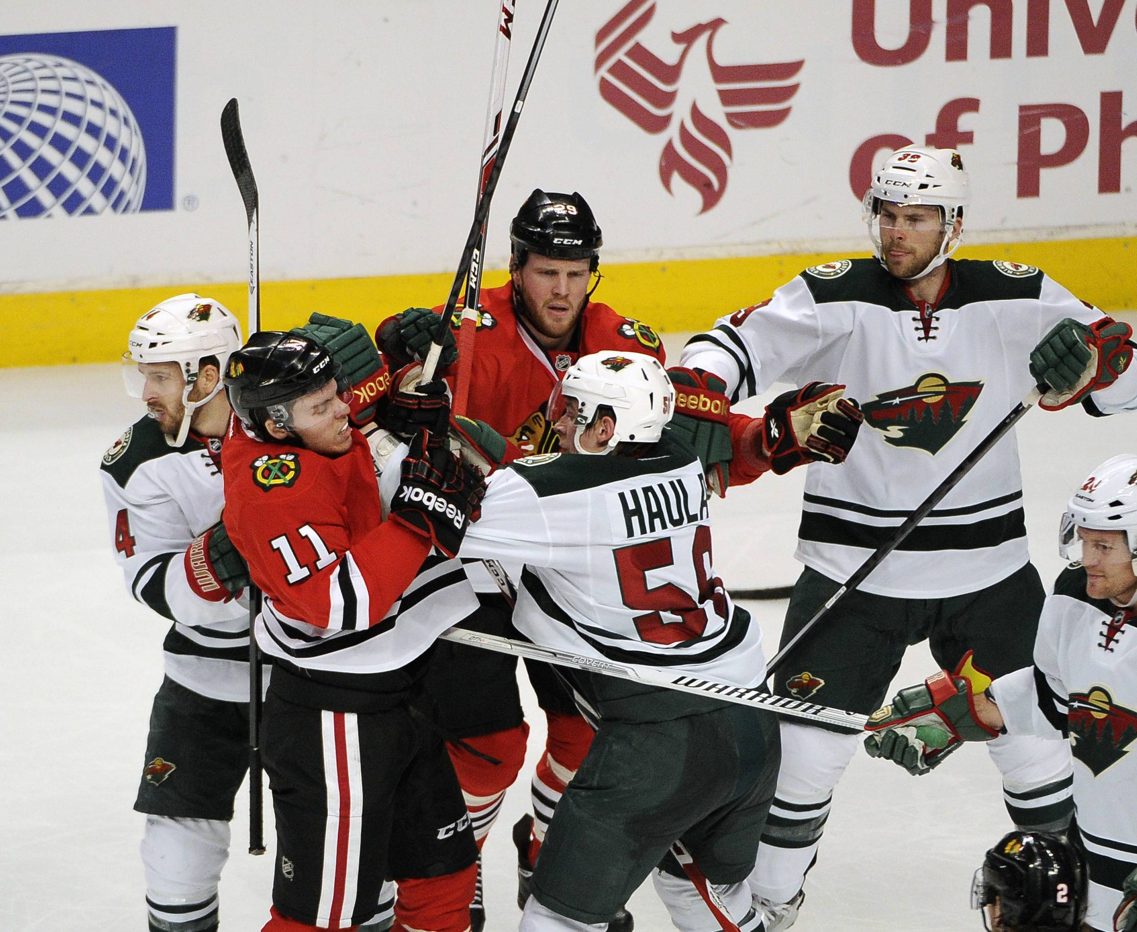 Blackhawks' Jeremy Morin (11) and Minnesota Wild's Erik Haula (56) get into an altercation in the second period of an NHL hockey game in Chicago, Thursday, April 3, 2014.