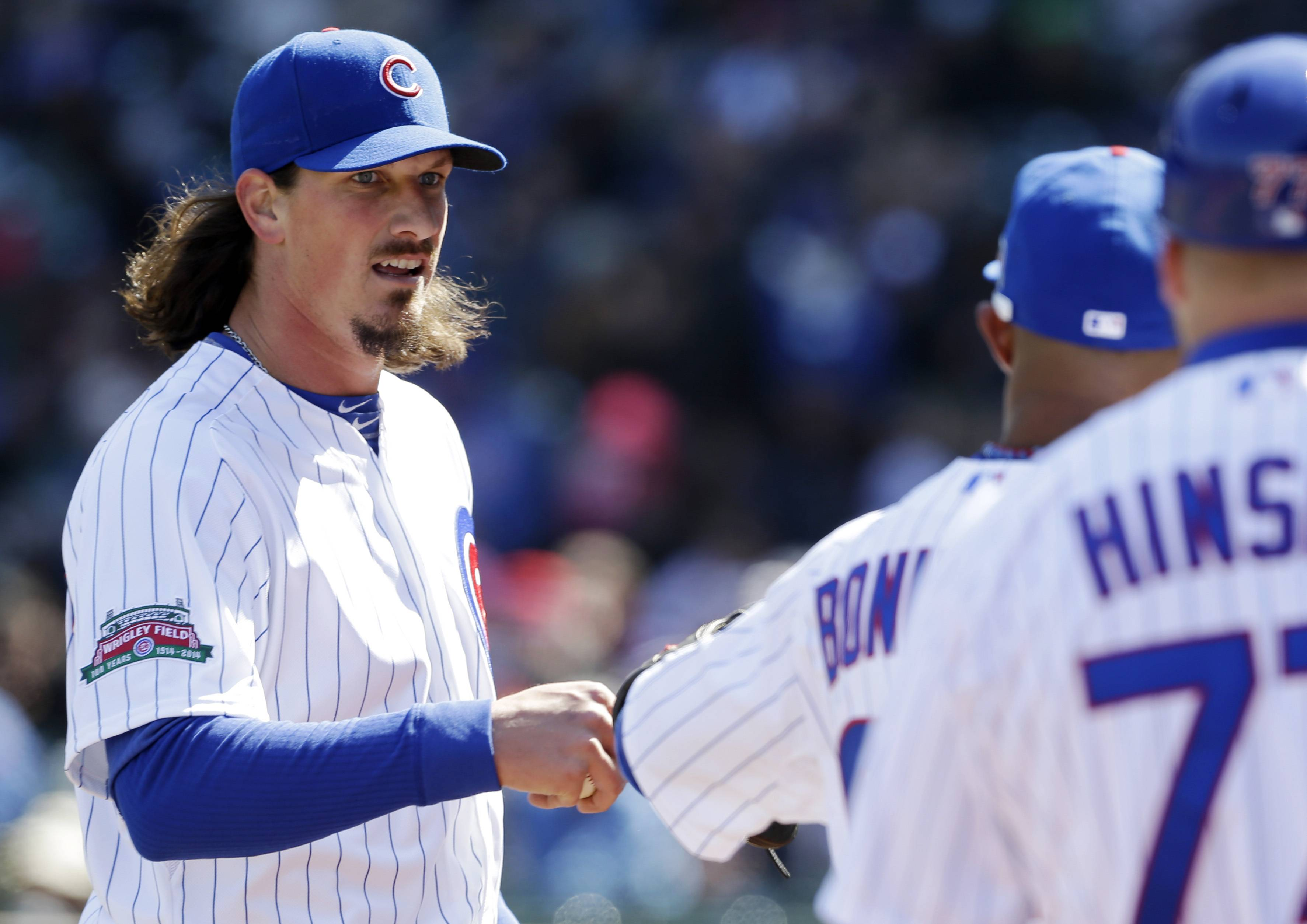 Chicago Cubs starter Jeff Samardzija, left, talks to Emilio Bonifacio as he walks walks back to the dugout during the third inning of a baseball game against the Philadelphia Phillies in Chicago, Saturday, April 5, 2014.