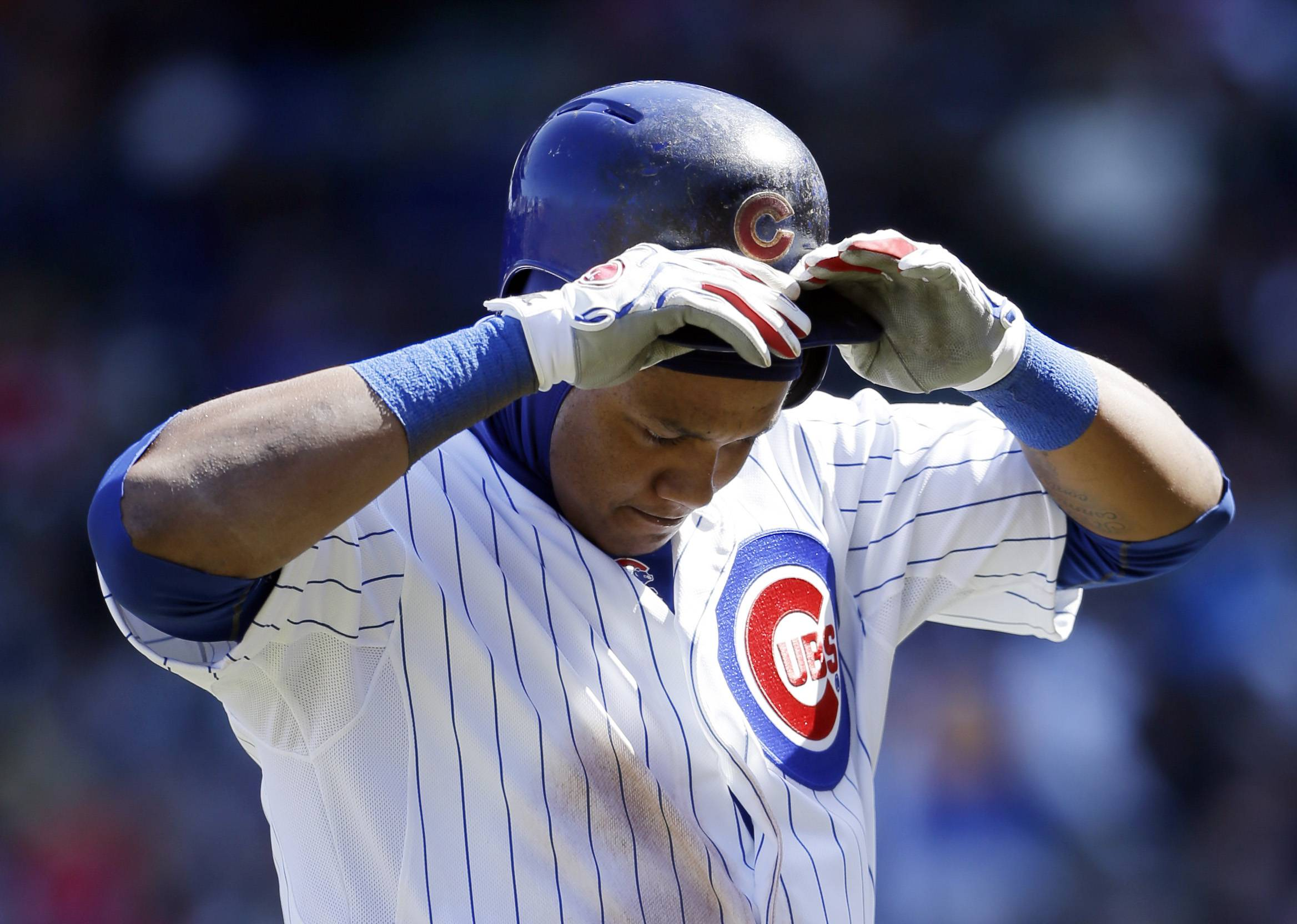 Chicago Cubs' Starlin Castro walks back to the dugout after getting out on a double play during the third inning of a baseball game against the Philadelphia Phillies in Chicago, Saturday, April  5, 2014. Emilio Bonifacio was out at second.