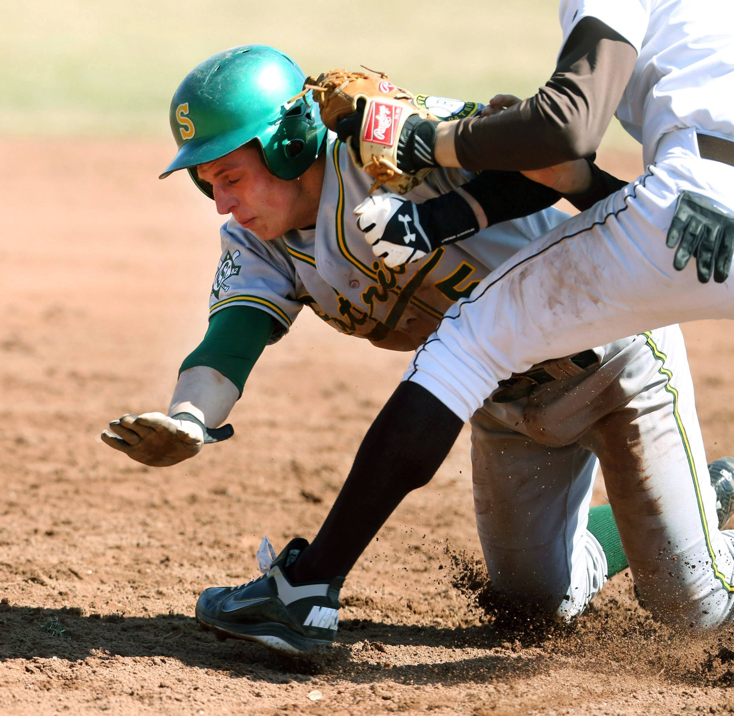 Stevenson's Aaron Saper is tagged out driving into third base by Carmel shortstop Andy Kantor at Carmel on Saturday in Mundelein.