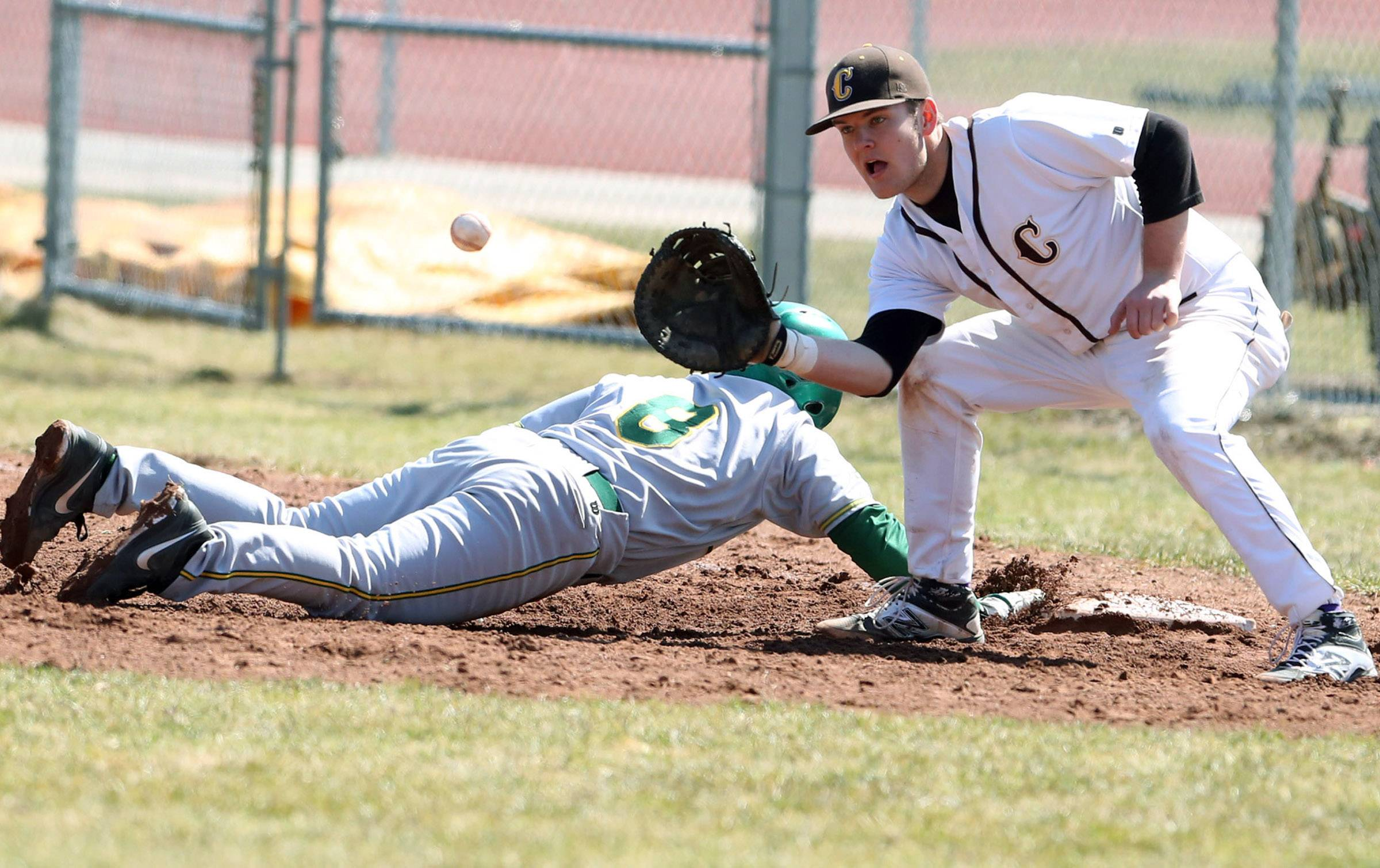 Stevenson's Michael Banakis dives safely back to first base as Carmel first baseman Andrew Wienke waits for the ball on Saturday in Mundelein.