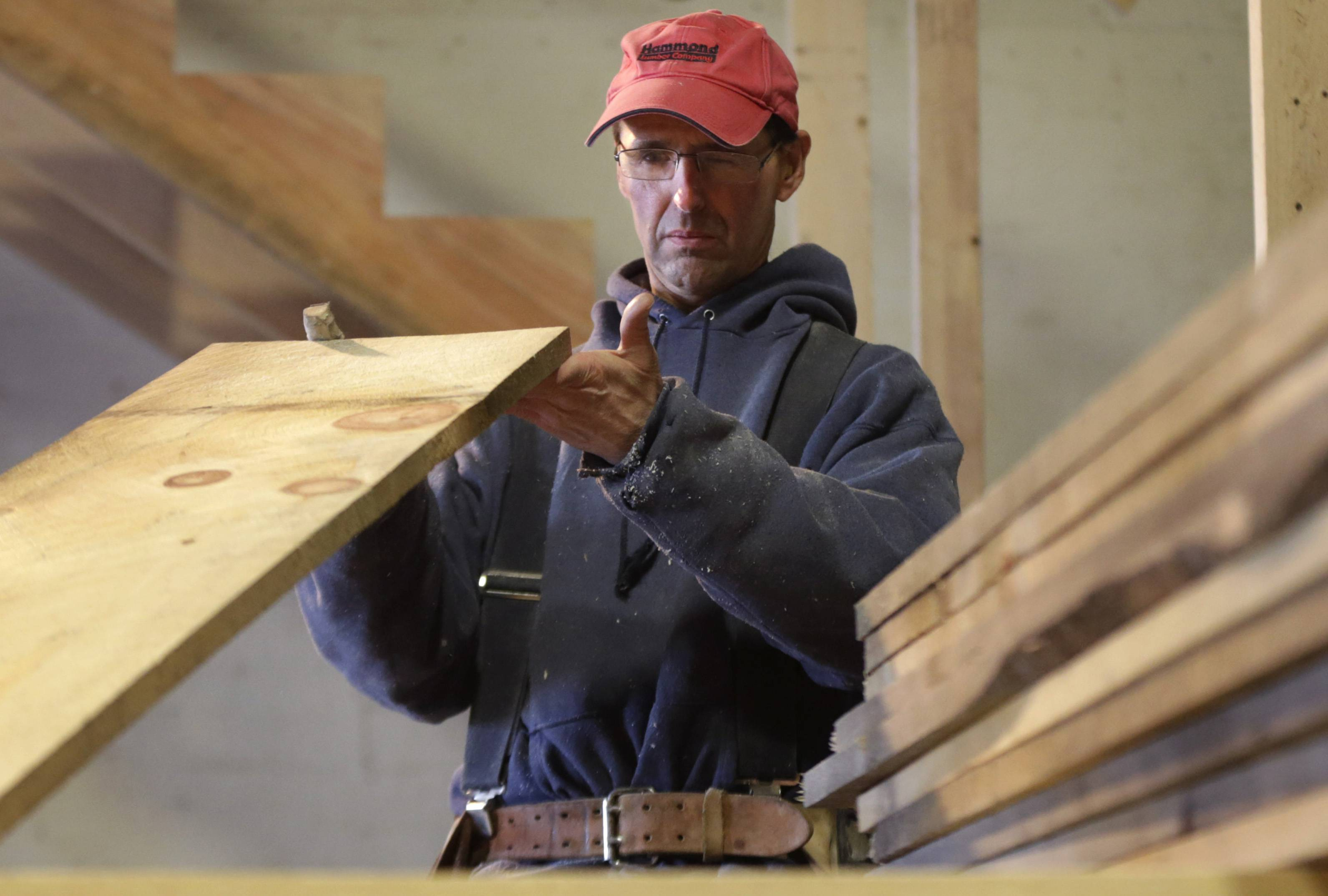 Ken Voorhees examines a board for defects while building a stairway for a customer in Lisbon, Maine. Voorhees, who is self-employed, signed up for health insurance with Maine Health Community Options. The nonprofit cooperative is capturing about 80 percent of the customers in the state seeking coverage under the health care law.