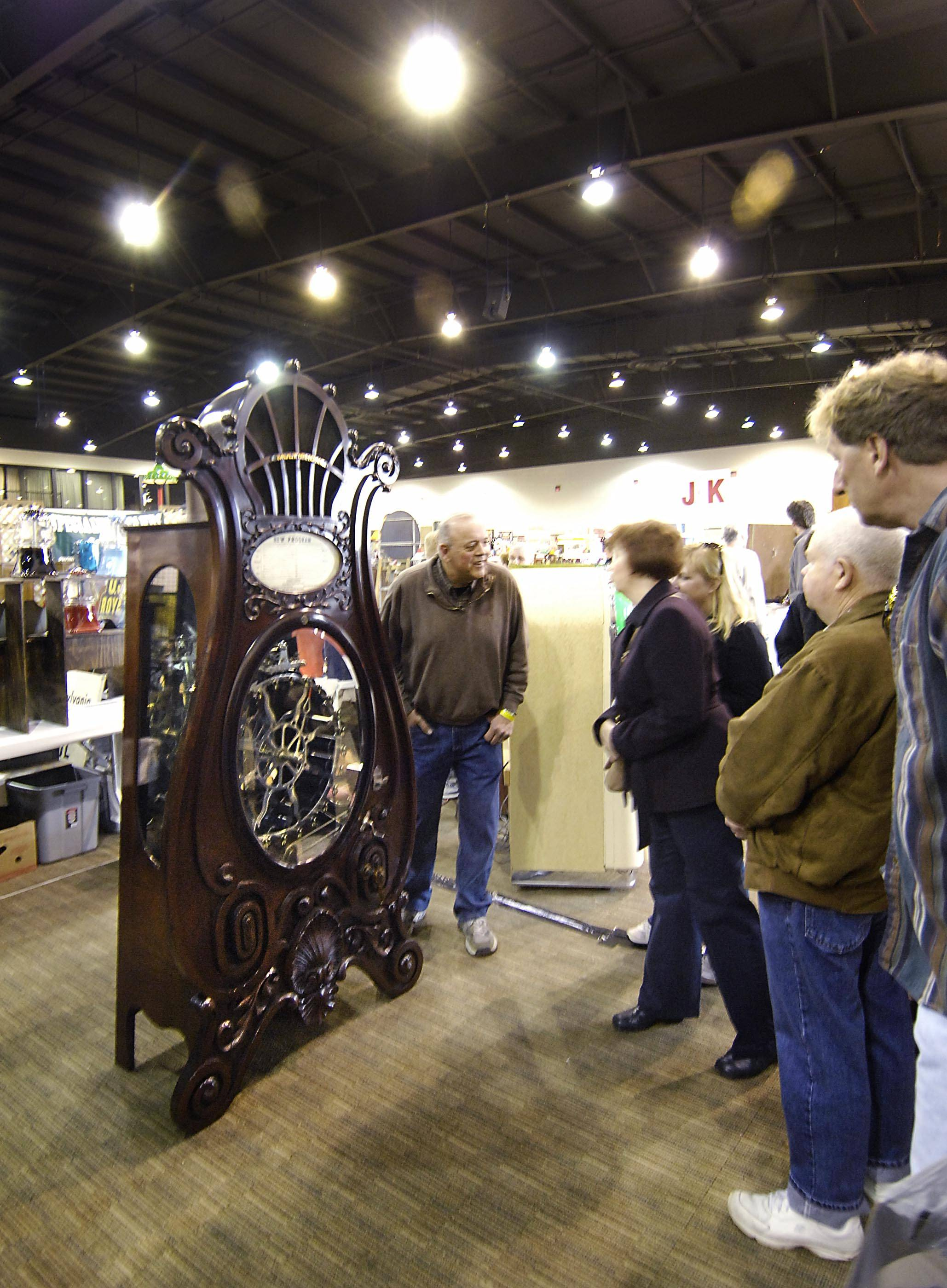 Paul Baker, of Buffalo, N.Y., answers questions about his 1907 Multiphone coin-operated phonograph Sunday at the Chicagoland Antique Advertising, Slot-Machine & Jukebox Show at the Pheasant Run Resort in St. Charles. Baker spent more than 700 hours restoring the mahogany music machine and was asking $135,000 for it.