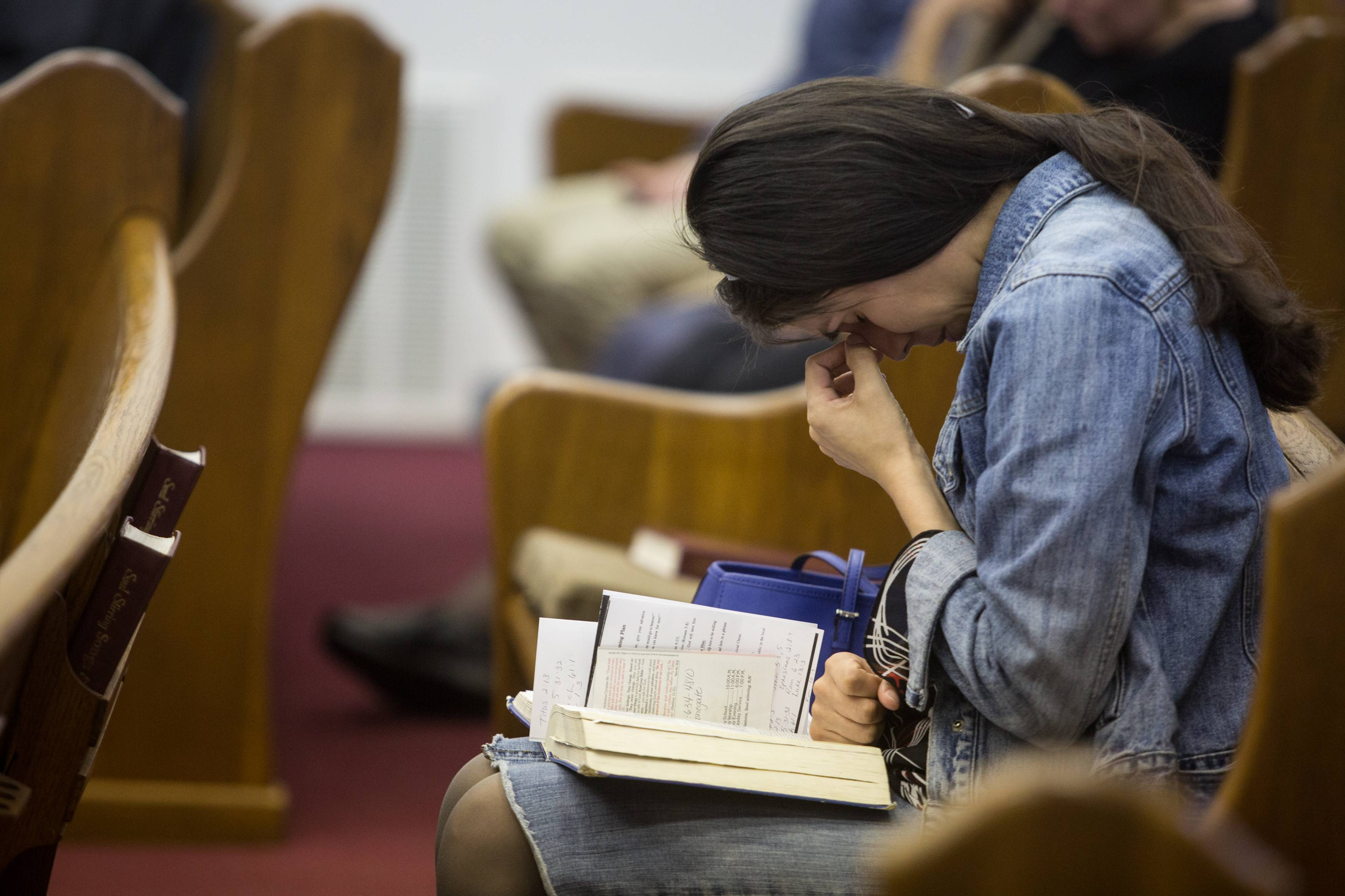 Kathy Abad, a military wife, prays for the victims and families affected by the Fort Hood shooting during a memorial service at the Tabernacle Baptist Church on Sunday in Killeen, Texas.