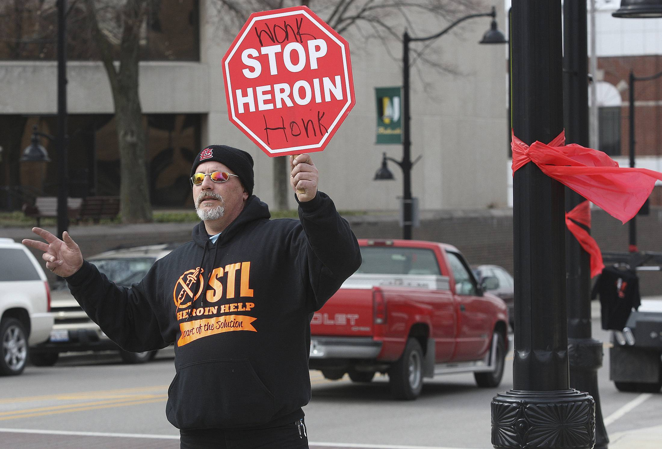 Phil Wahby, of St. Louis, an outreach coordinator with the STLHeroinHelp organization, waves to motorists during an anti-heroin rally in Belleville, Ill. Coroners from the Chicago area to St. Louis' Illinois suburbs say heroin overdose deaths have spiked in recent years, given the relative cheapness, purity, potency and broad availability.