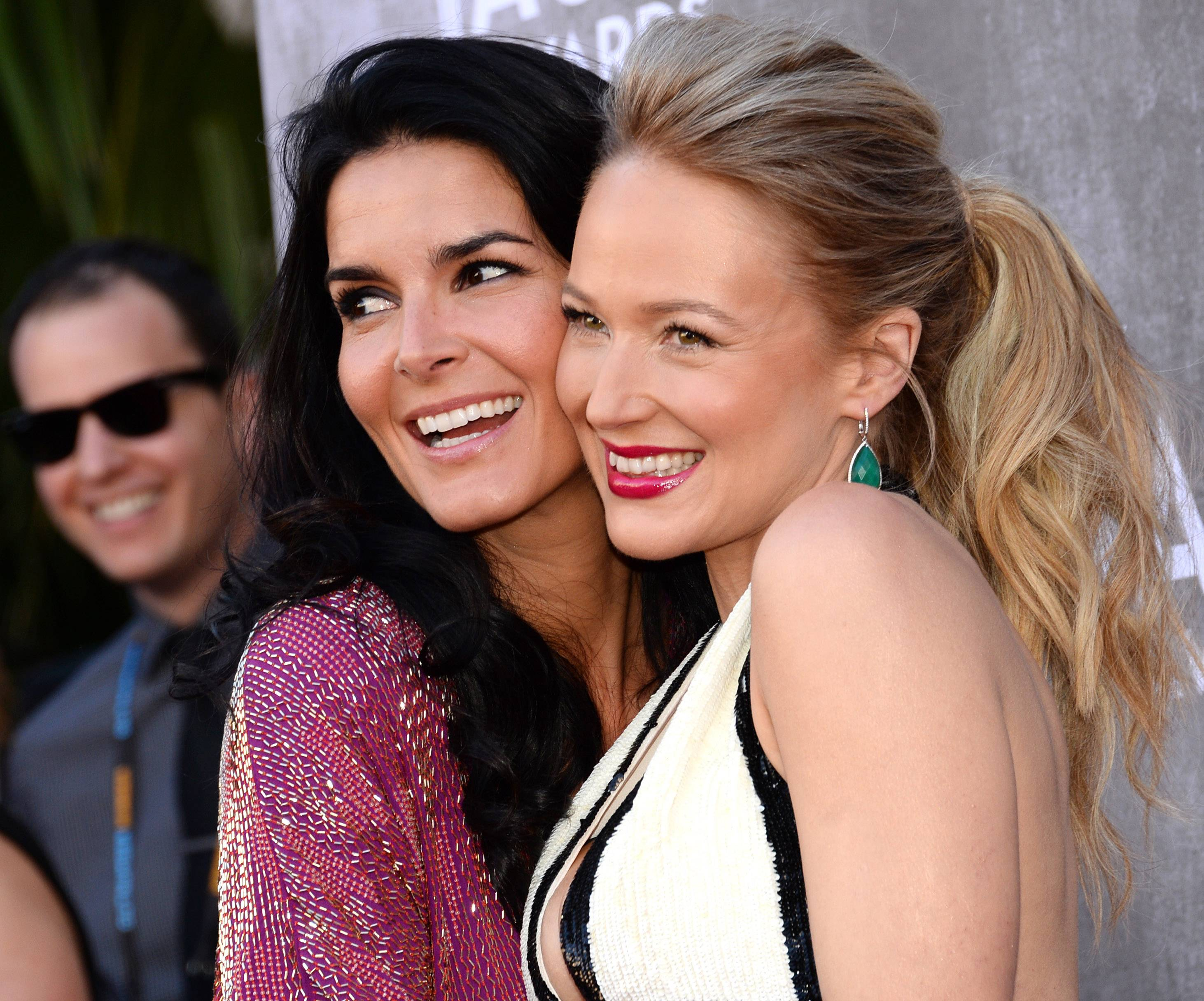 Angie Harmon, left, and Jewel share a moment on their way into the 49th annual Academy of Country Music Awards.