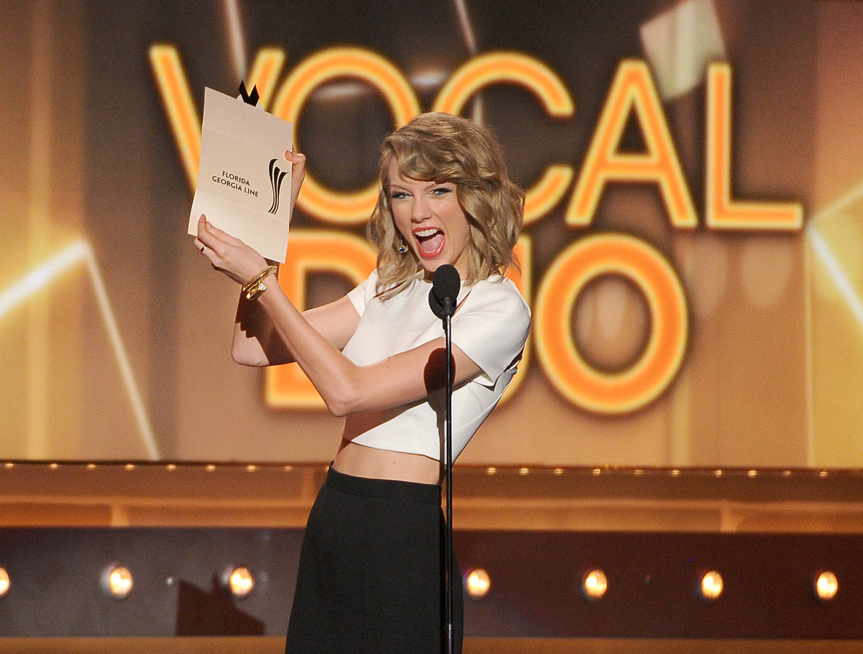 Taylor Swift presents the vocal duo of the year award to Florida Georgia Line at the 49th annual Academy of Country Music Awards.