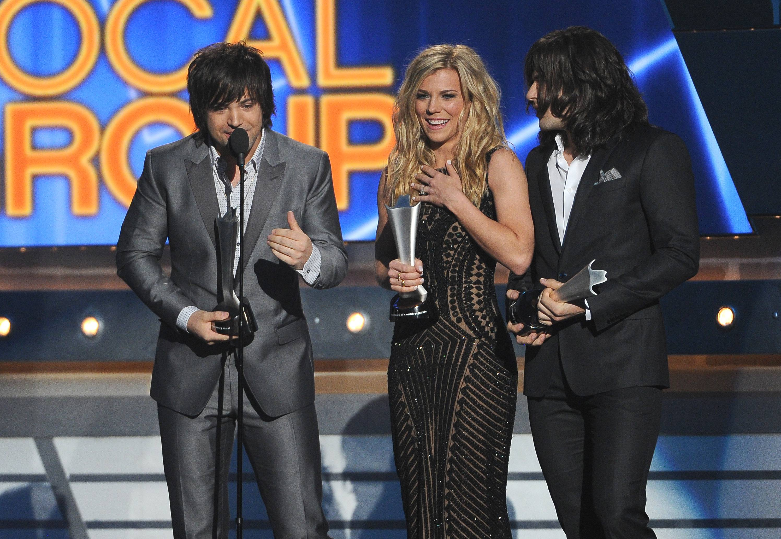 Neil Perry, and from left, Kimberly Perry and Reid Perry, of the musical group The Band Perry, accept the award for vocal group of the year at the 49th annual Academy of Country Music Awards.