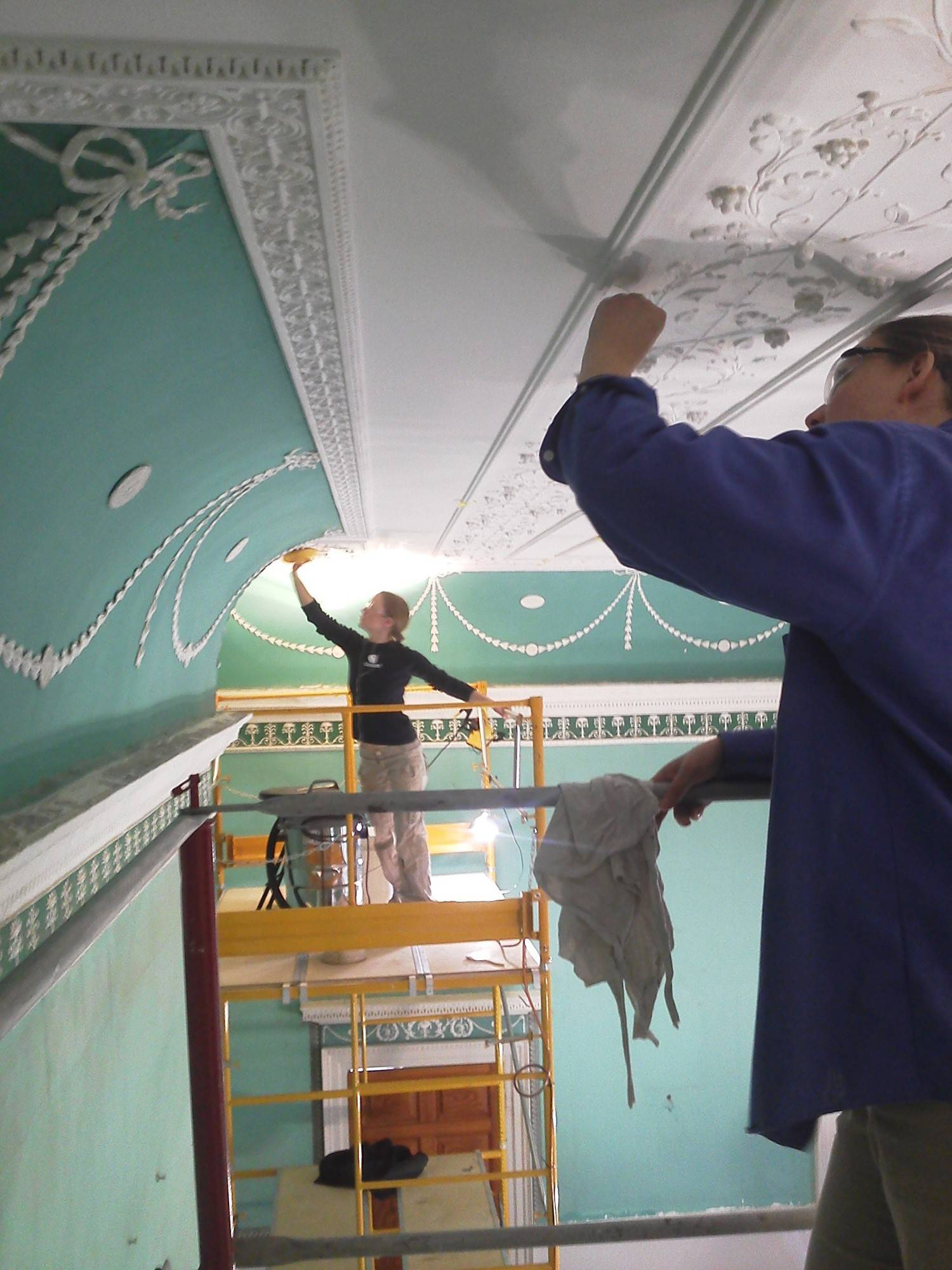 "Architectural paint conservators Maeve Bristow and Amelia Jensen work on the ceilings in the restored ""New Room"" at Mount Vernon."