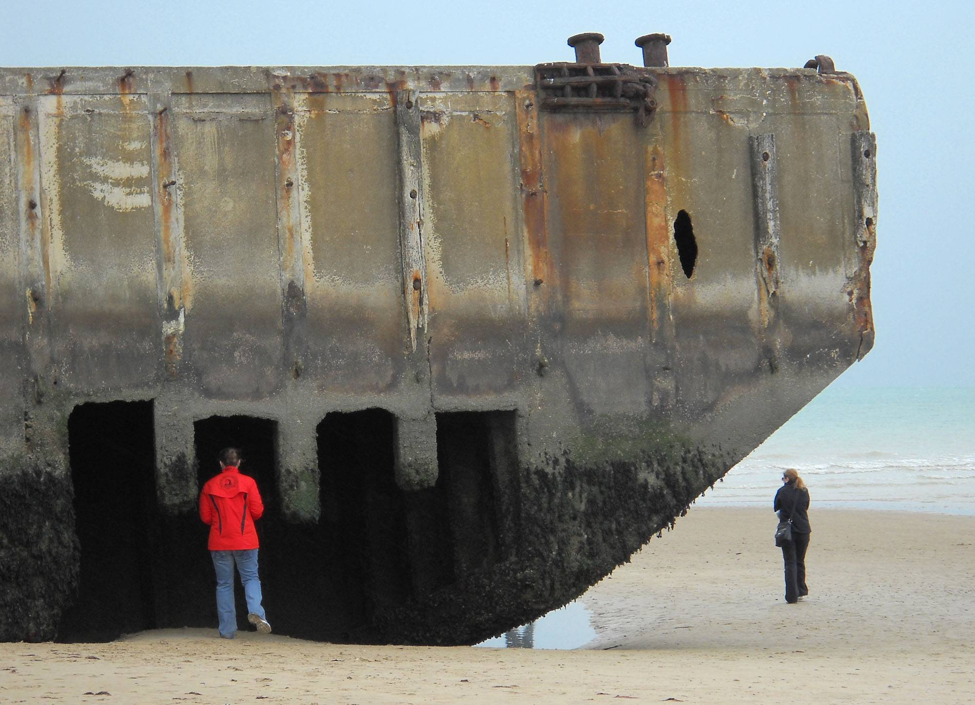 A visitor inspects the remains of an artificial harbor used by Allied forces during World War II on the sand at Arromanches, France. Arromanches is one of several beaches on the coast of Normandy likely to see an influx of tourists for the 70th anniversary of D-Day on June 6, 2014.