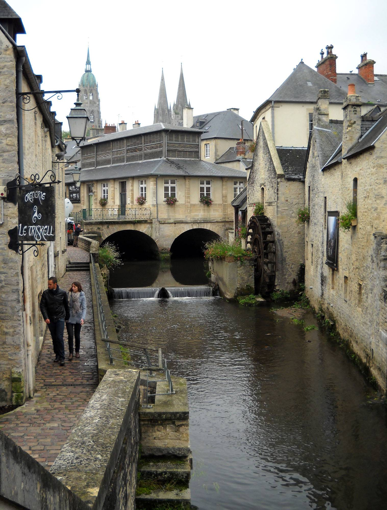 People walk along the Aure River in Bayeux. The old town center boasts cobblestone streets, upscale shops, small eateries and picturesque mills along the narrow river.