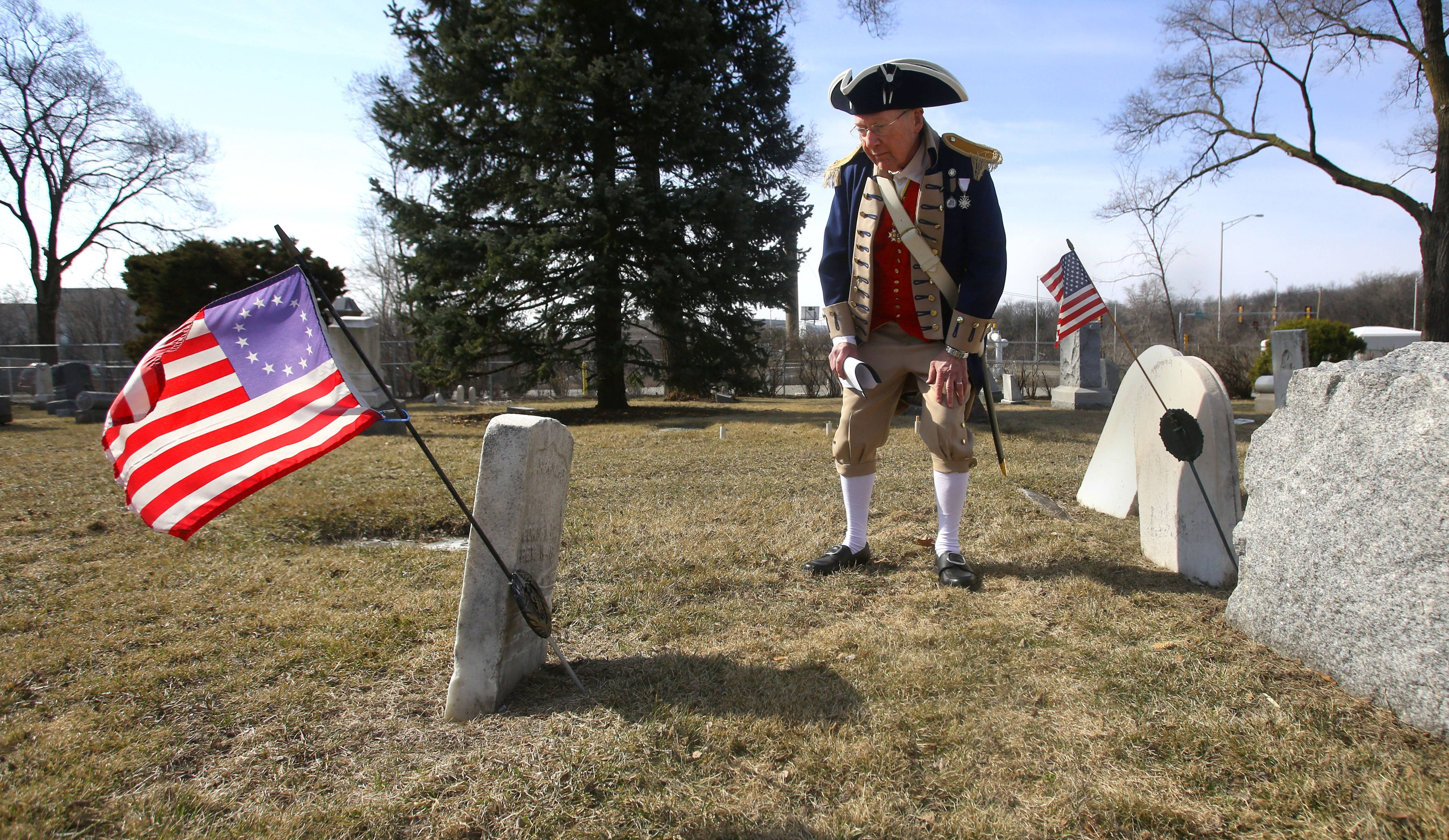 The Illinois Society Sons of the American Revolution installed historical markers Sunday at Elk Grove Cemetery, recognizing two Revolutionary War figures buried there. Above, Franz Herder observes the gravesite of Revolutionary War patriot Aaron Miner.