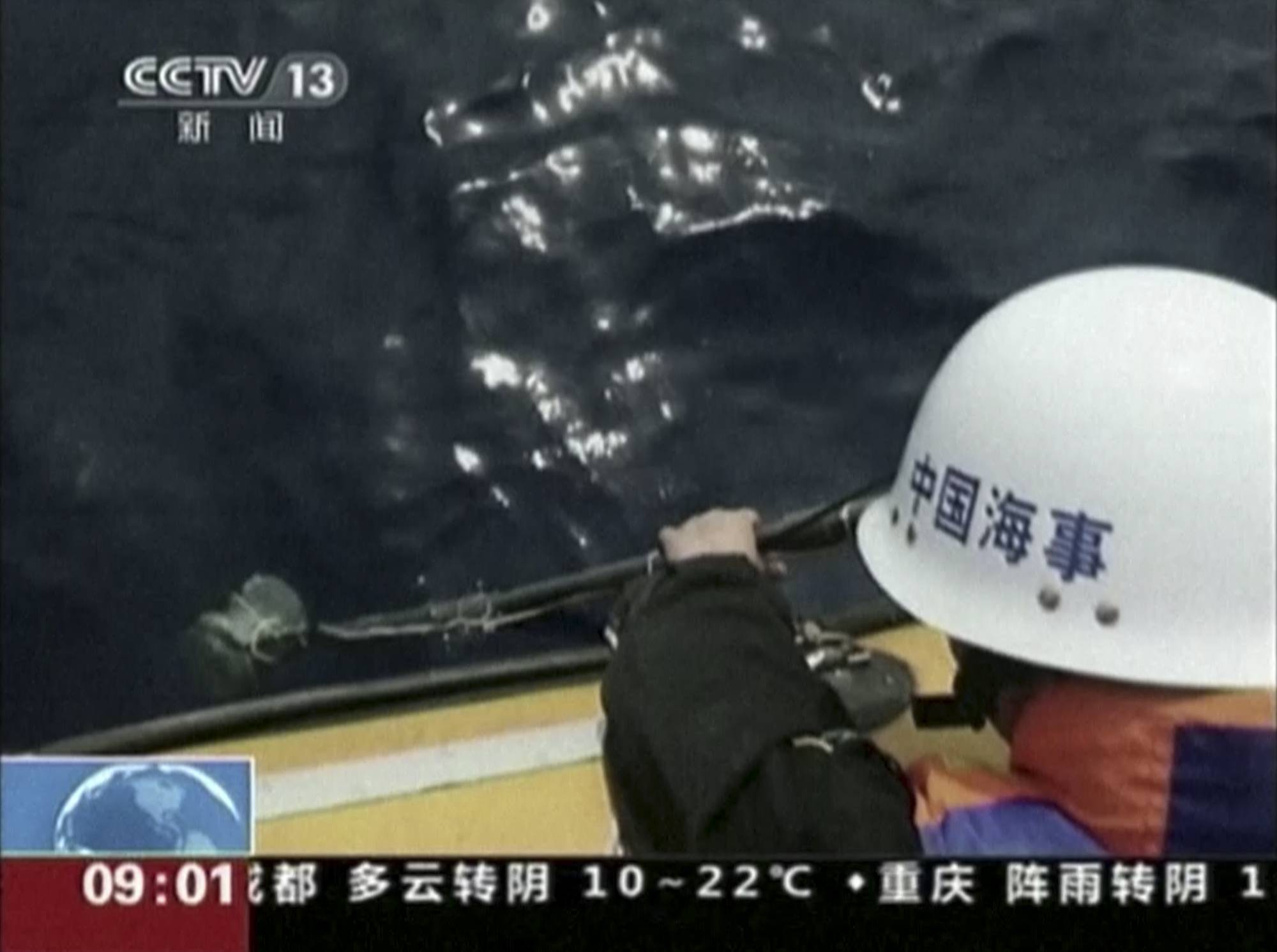 A member of a Chinese search team uses an instrument to detect electronic pulses while searching for the missing Malaysia Airlines Flight 370 on board a patrol vessel in the search area of the southern Indian Ocean Saturday.