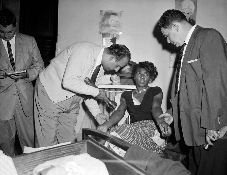 In this Sept. 22, 1957 file photo, police Detectives John Matassa, center and Sheldon Teller, right, examine the arms of a suspected narcotics addict and dealer in New York. Eric Schneider, a professor at the University of Pennsylvania said after World War II, heroin became a drug primarily used by blacks and Puerto Ricans in the Northeast and by Mexican Americans in the West.