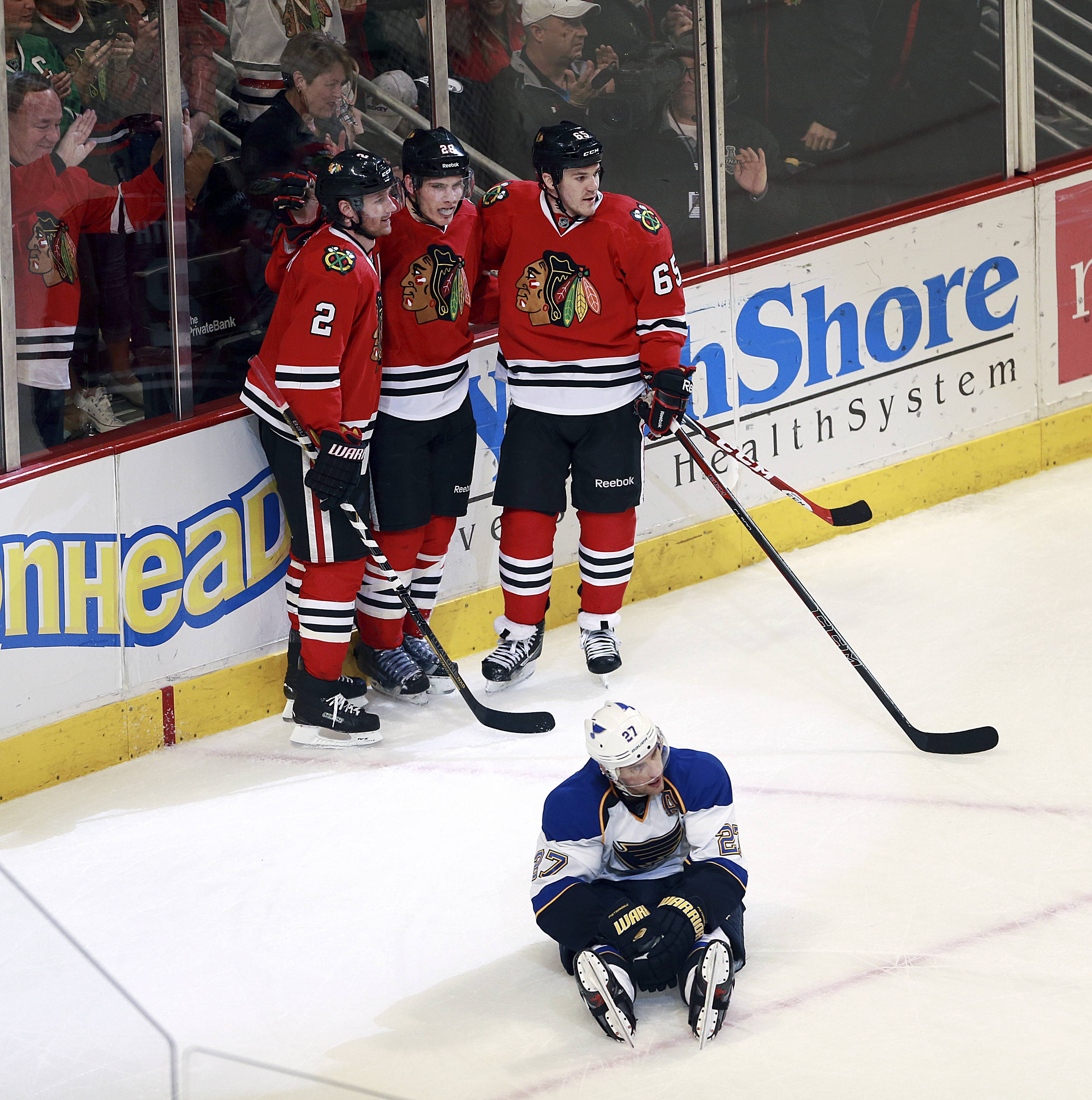 Chicago Blackhawks' Duncan Keith, left, Ben Smith, center, and Andrew Shaw celebrate after Smith's empty net goal as St Louis Blues' Alexander Pietrangelo, front, sits on the ice in the third period of an NHL hockey game in Chicago on Sunday, April 6, 2014. The Blackhawks won 4-2.