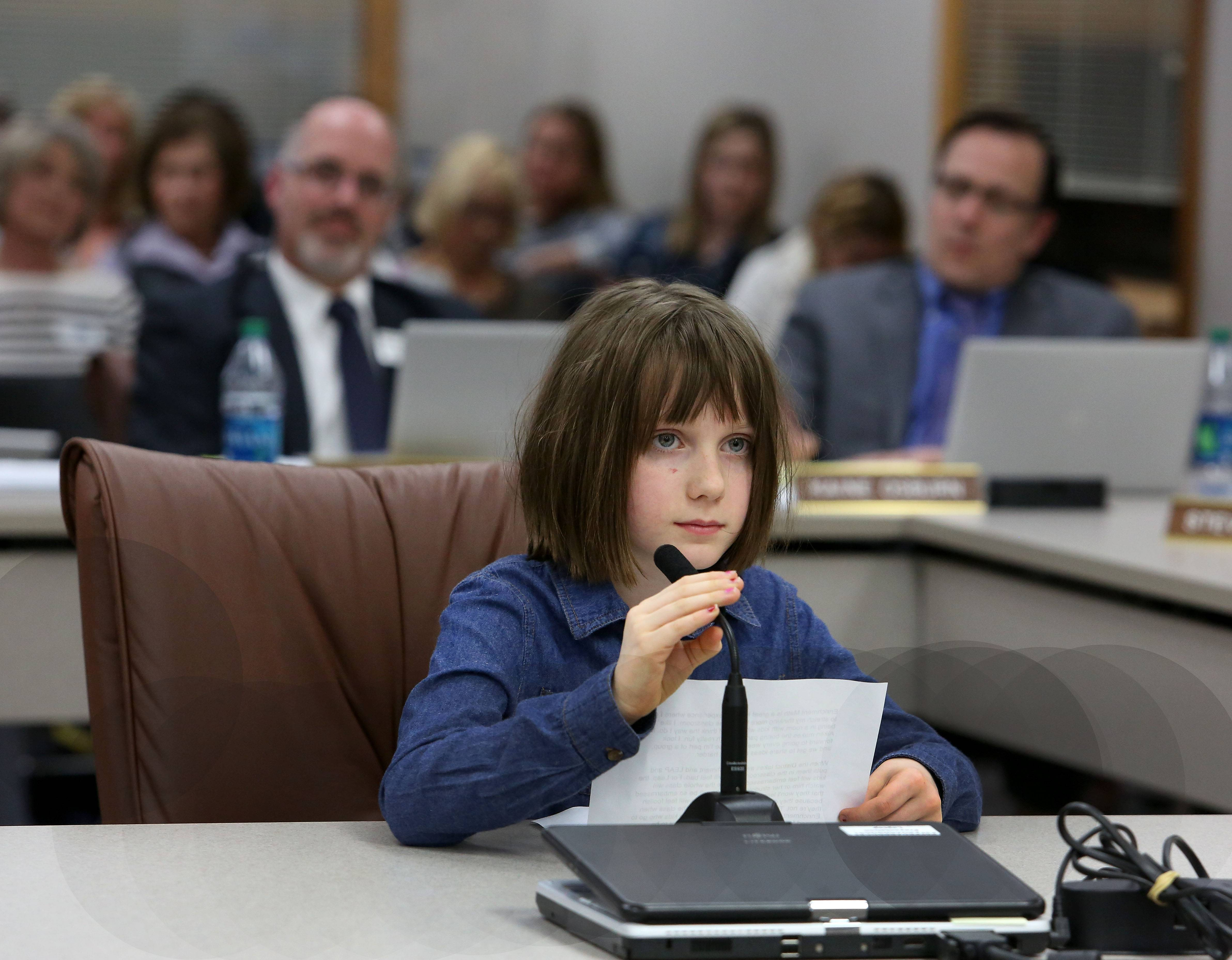 "Annie Ayoub, 8, a third-grader at Beebe Elementary in Naperville Unit District 203, speaks to the school board Monday night in favor of retaining enrichment programs in which students leave the classroom to receive additional challenges in a small-group setting. ""I like being in a room with other kids who kind of think how I do,"" Annie said about the students in her math enrichment group. ""I look forward to going every week because I'm part of a group and we get to share ideas and think harder."""