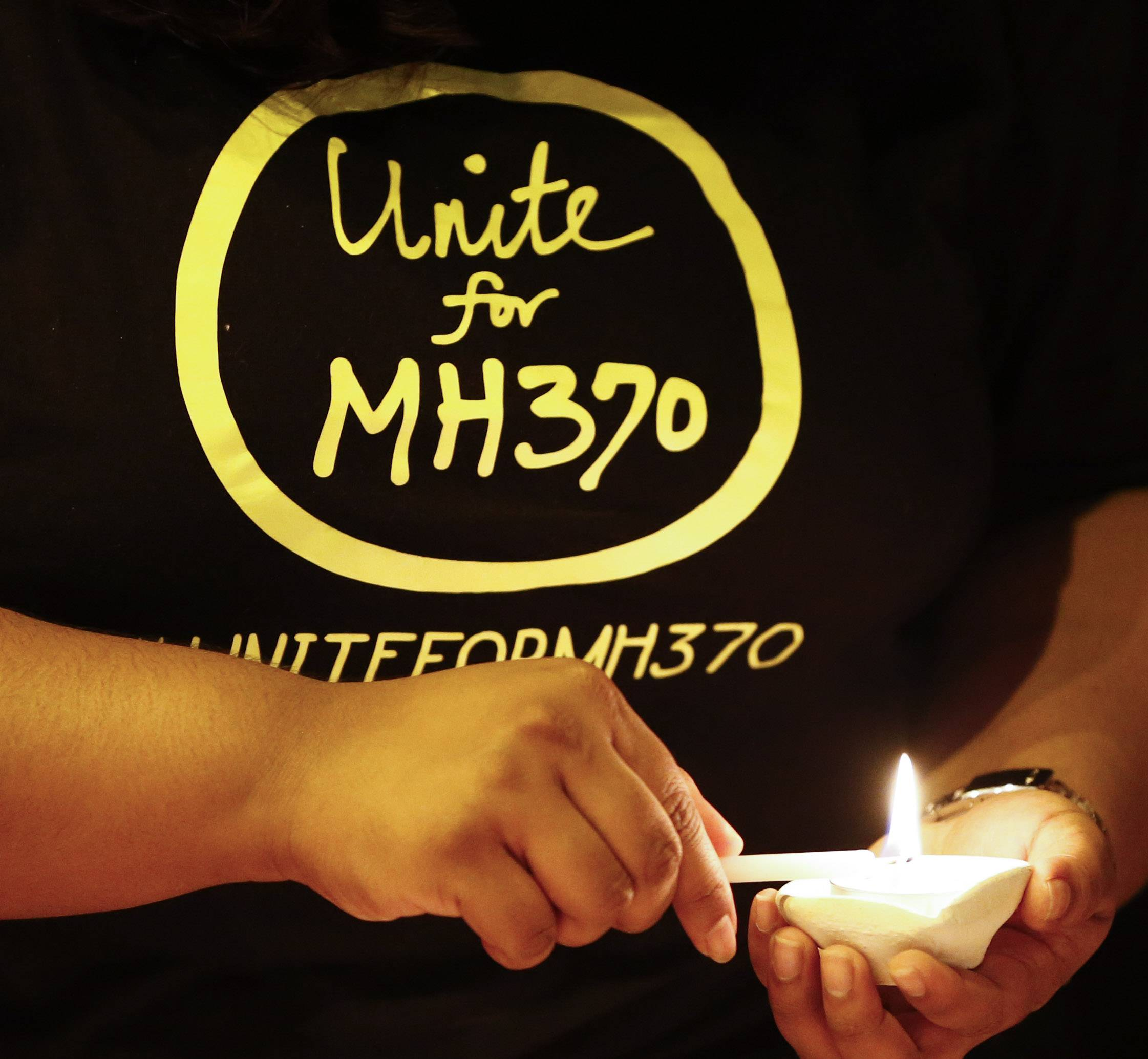 A woman lights a candle during a candlelight vigil for passengers onboard the missing Malaysia Airlines Flight MH370, in Kuala Lumpur, Malaysia, Monday, April 7, 2014. An Australian ship detected two distinct, long-lasting sounds underwater that are consistent with the pings from aircraft black boxes in a major break in the month long hunt for the missing Malaysia Airlines jet, the search coordinator said Monday.