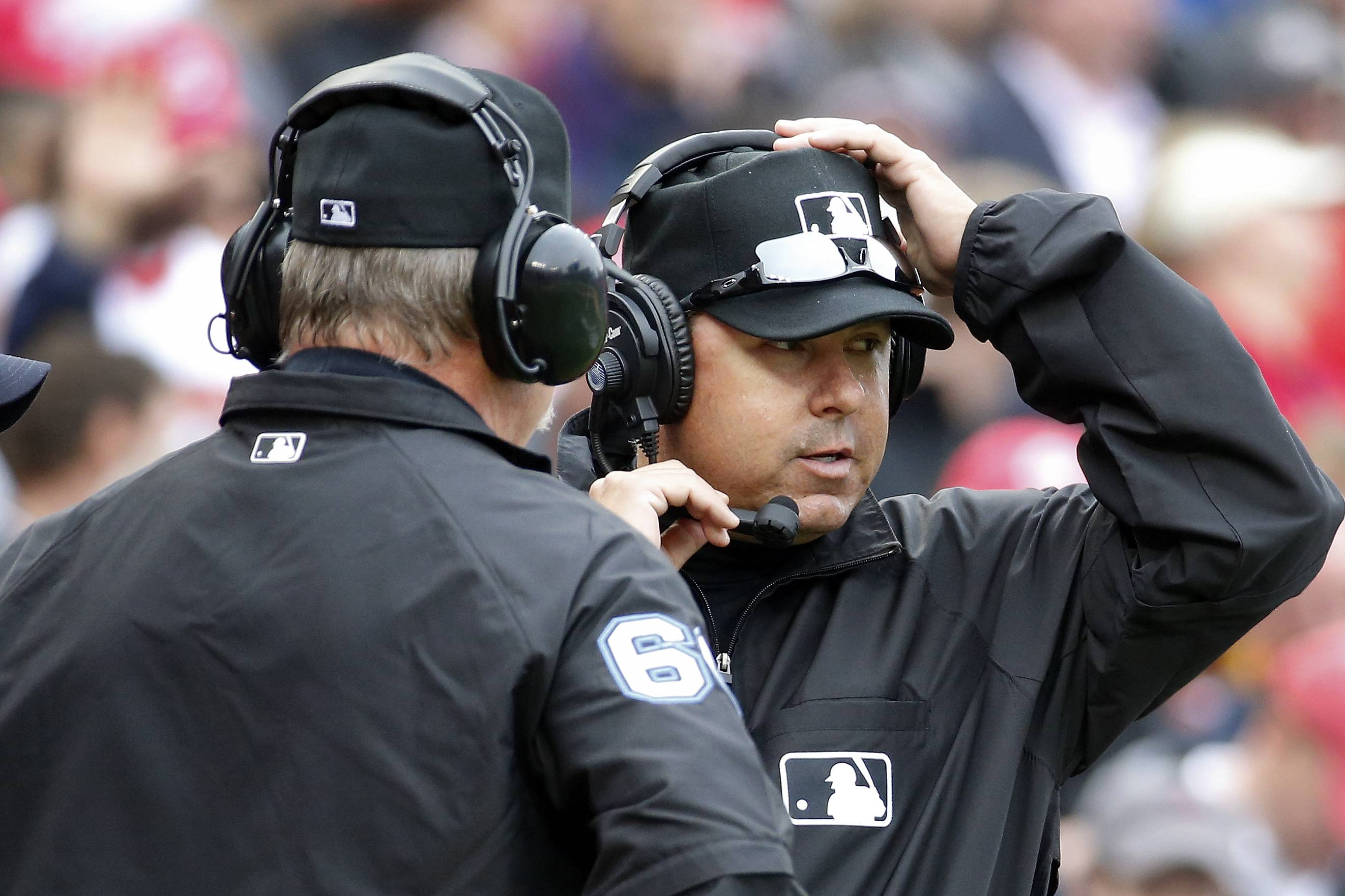 Umpires Jim Joyce, left, and Doug Eddings talk on head phones as they review a call during the fifth inning of a game between the Washington Nationals and Atlanta Braves on Friday. Ian Desmond's inside-the-park homer was overturned on replay review and changed to a ground-rule double.