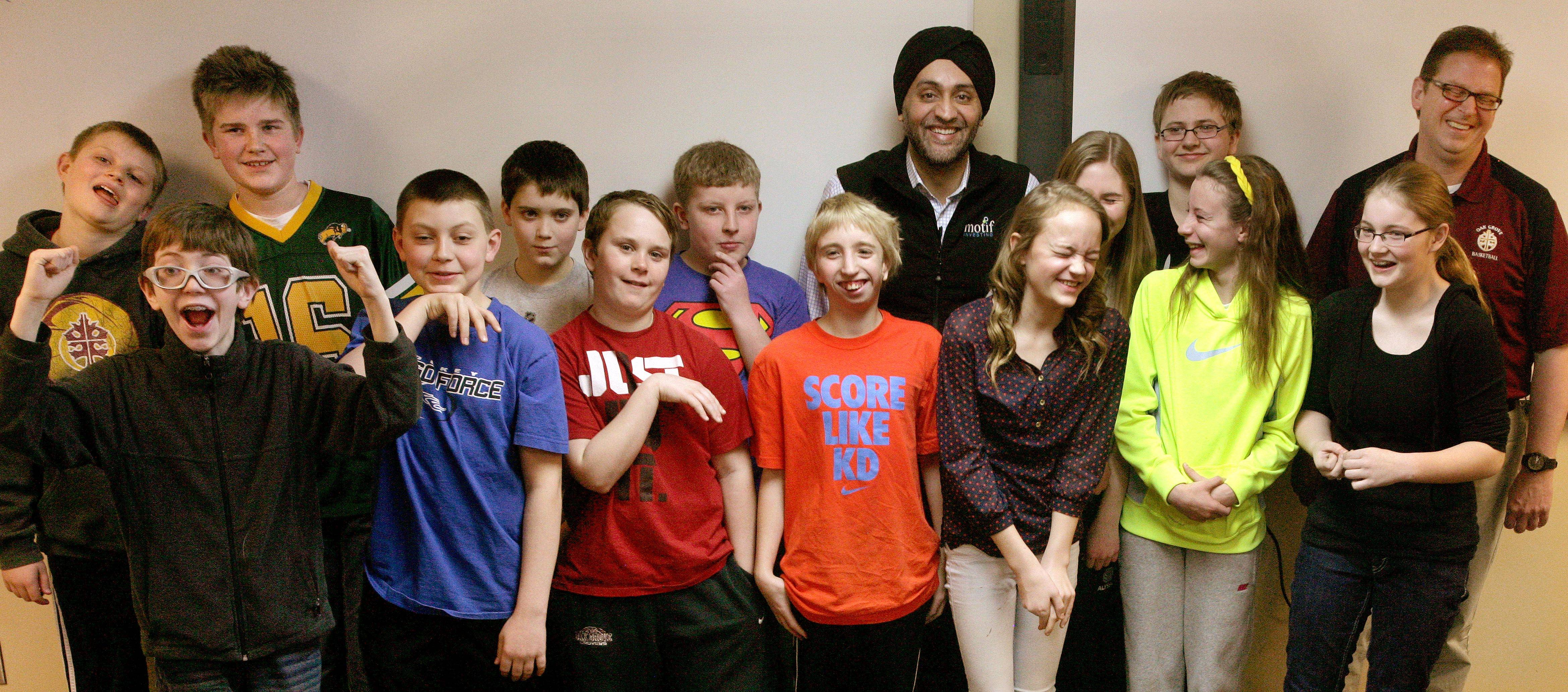 The Math Minions, sixth graders at Oak Grove Middle School in Fargo, N.D., pose with Motif Investing founder Hardeep Walia, center right rear, and math teacher Dave Carlson, right rear. Carlson started a competition between regular and advance math classes at Oak Grove and registered his students with Motif Investing, a company that enables customers to buy baskets of stocks. In the end, Carlson's regular math class yielded a nearly 22 percent gain and trounced every university club participating in the contest.