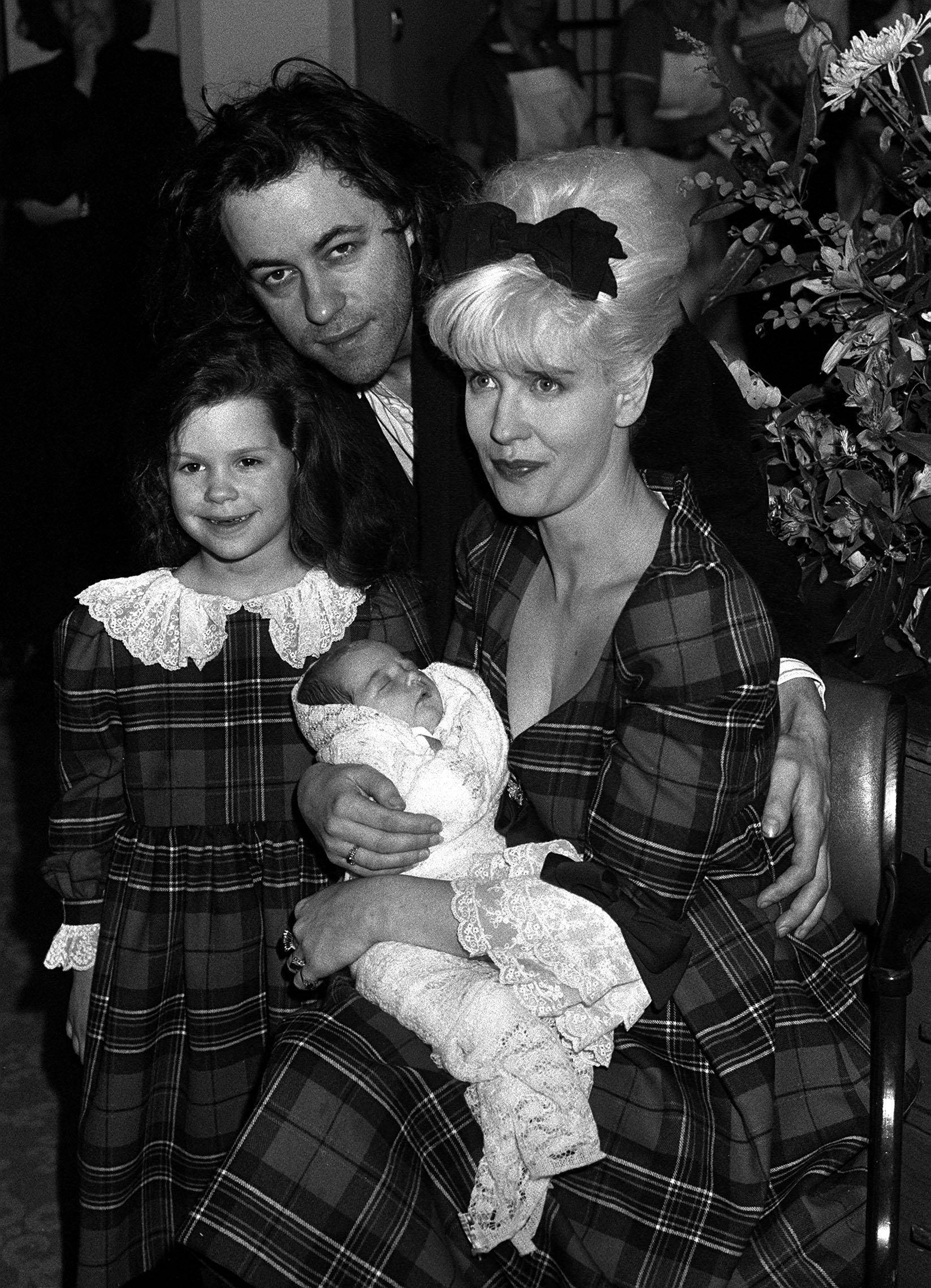 "In this March 16, 1989 file photo rock star Bob Geldof, his wife, TV presenter Paula Yates, right, and their five-year-old daughter Fifi Trixiebelle, left, show off the new addition to their family, an as yet unnamed baby girl, later named Peaches, at St Mary's Hospital in Paddington, London. Peaches Geldof, the model and television presenter who was concert organizer Bob Geldof's daughter, has died at age 25. Bob Geldof said in a statement Monday, April 7, 2014: ""Peaches has died. We are beyond pain."""