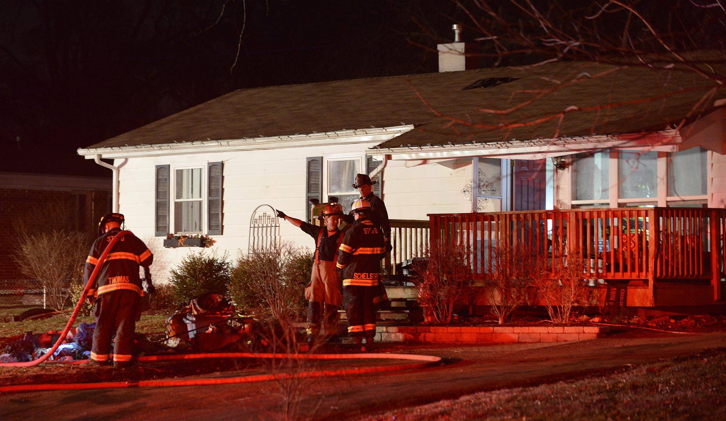 St. Charles firefighters stand in front of a home on S. 4th Pl. near Moore Ave. Monday evening after putting out a fire.