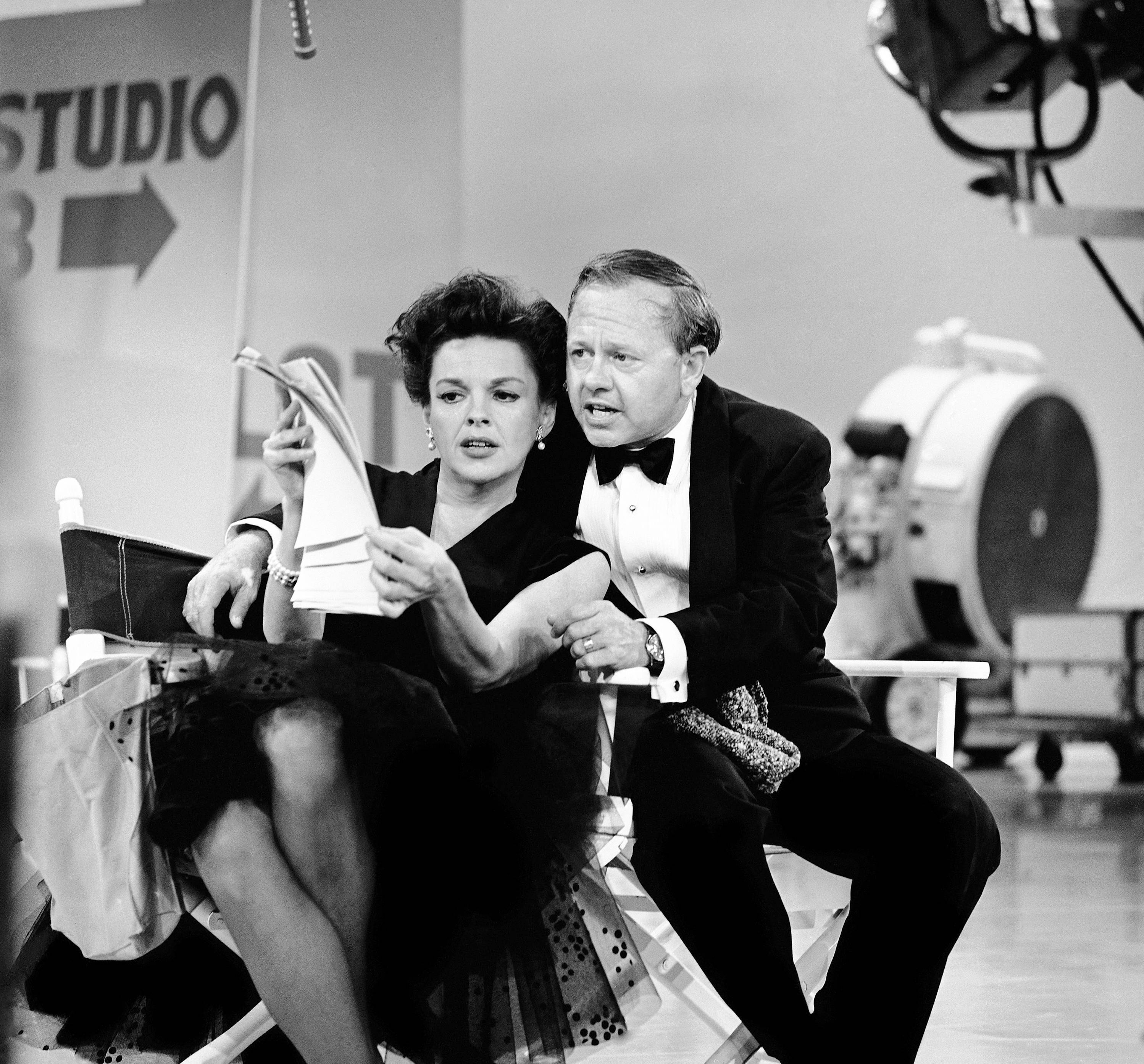 In this June 26, 1963, file photo, Judy Garland and Mickey Rooney put their heads together over a television script for their first onstage reunion in 18 years, for the taping of the first of 32 variety shows which Garland will do for CBS next season.