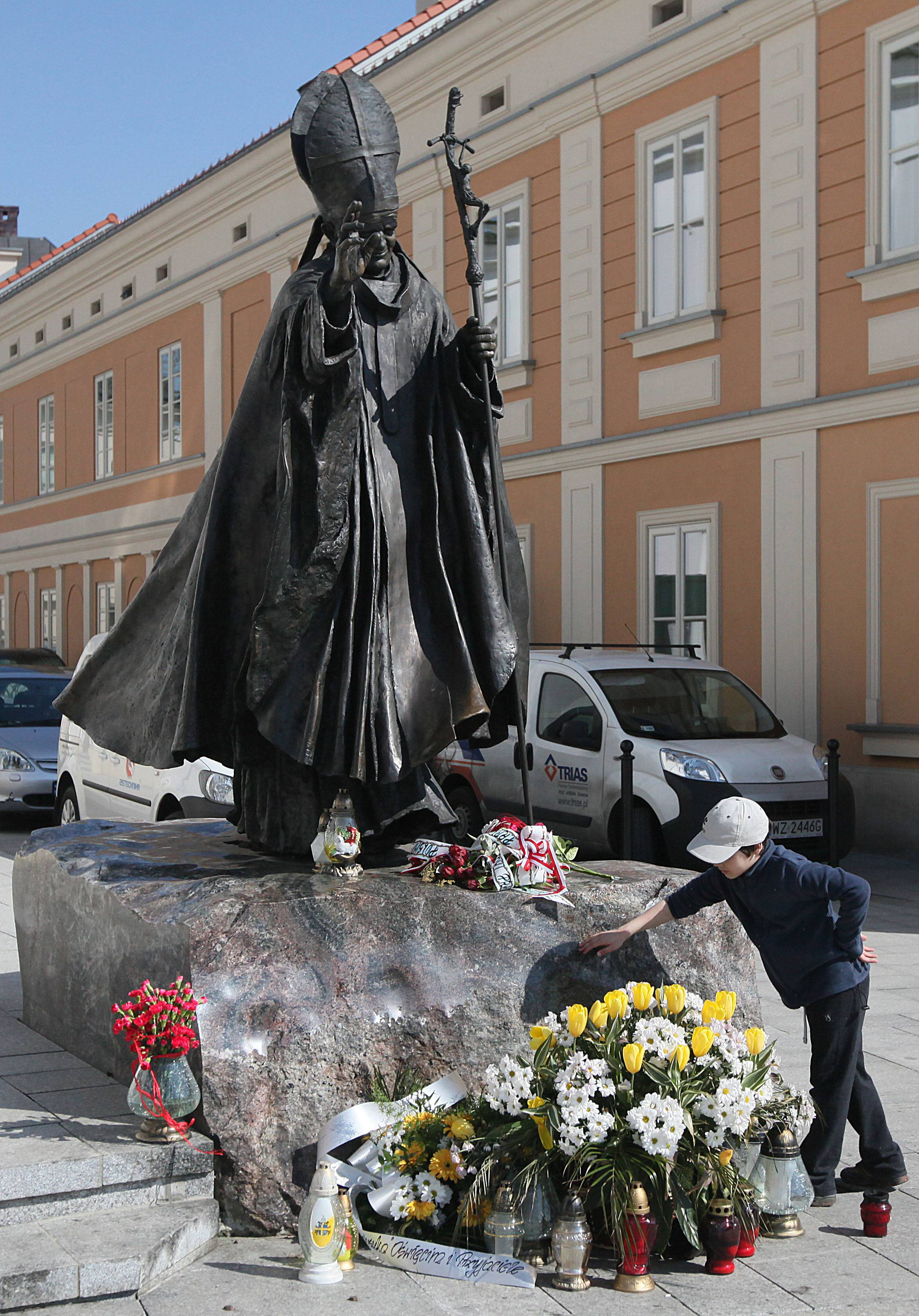 The figure of blessed Pope John Paul II is pictured before the Holy Mary' Offering Basilica where he was baptized as an infant in Wadowice, Poland, on Monday, April 7, 2014. The basilica neighbors the house where the pope was born as Karol Wojtyla in 1920 and where a multimedia museum will open in his memory on Wednesday, just over two weeks before he will be made a saint in a Vatican ceremony April 27.
