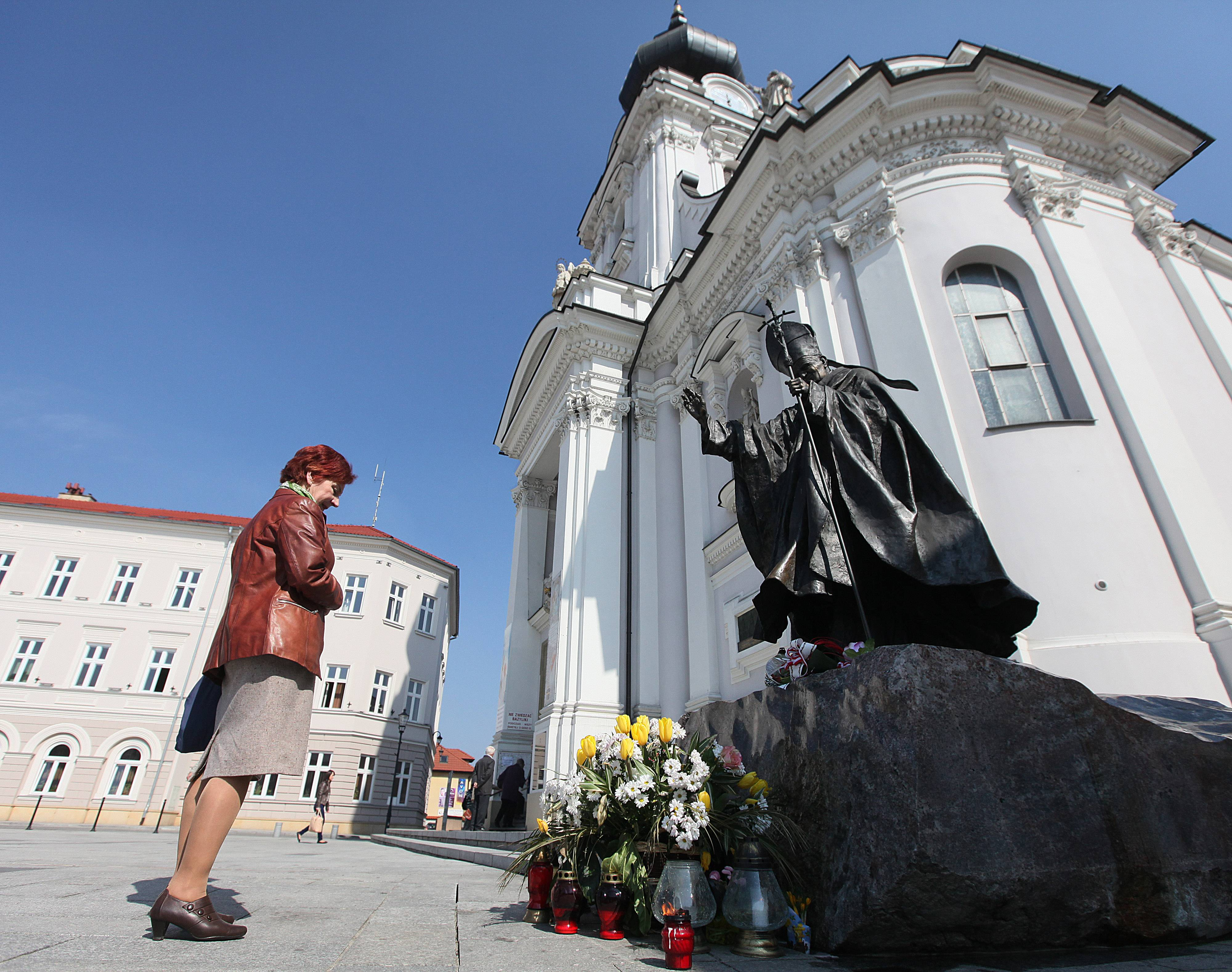 A woman stands in front of the figure of blessed Pope John Paul II before the Holy Mary' Offering Basilica where he was baptized as an infant in Wadowice, Poland, on Monday, April 7, 2014. The basilica neighbors the house where the pope was born as Karol Wojtyla in 1920 and where a multimedia museum will open in his memory on Wednesday, just over two weeks before he will be made a saint in a Vatican ceremony April 27.