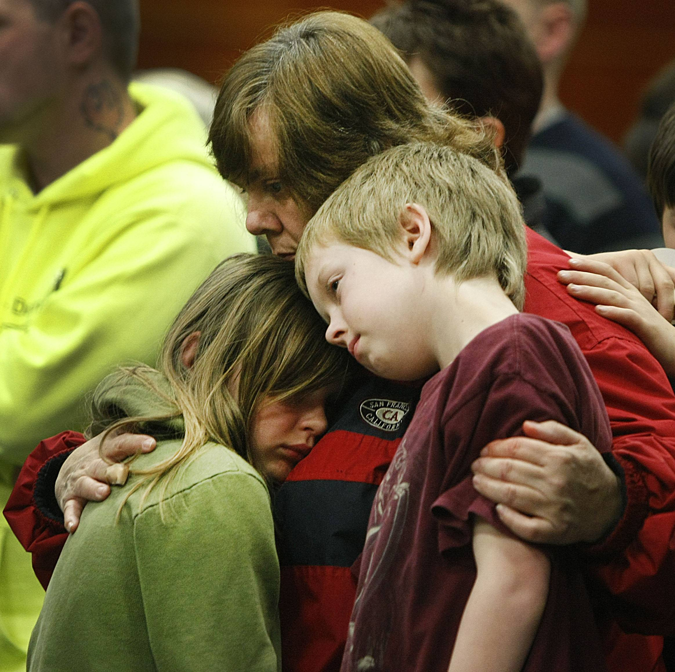 Members of the community embrace during a candlelight vigil at the Darrington Community Center, Saturday, April 5, 2014, in Darrington, Wash. A candlelight vigil was held two weeks after the deadly mudslide that hit Oso and took at least 30 victims.