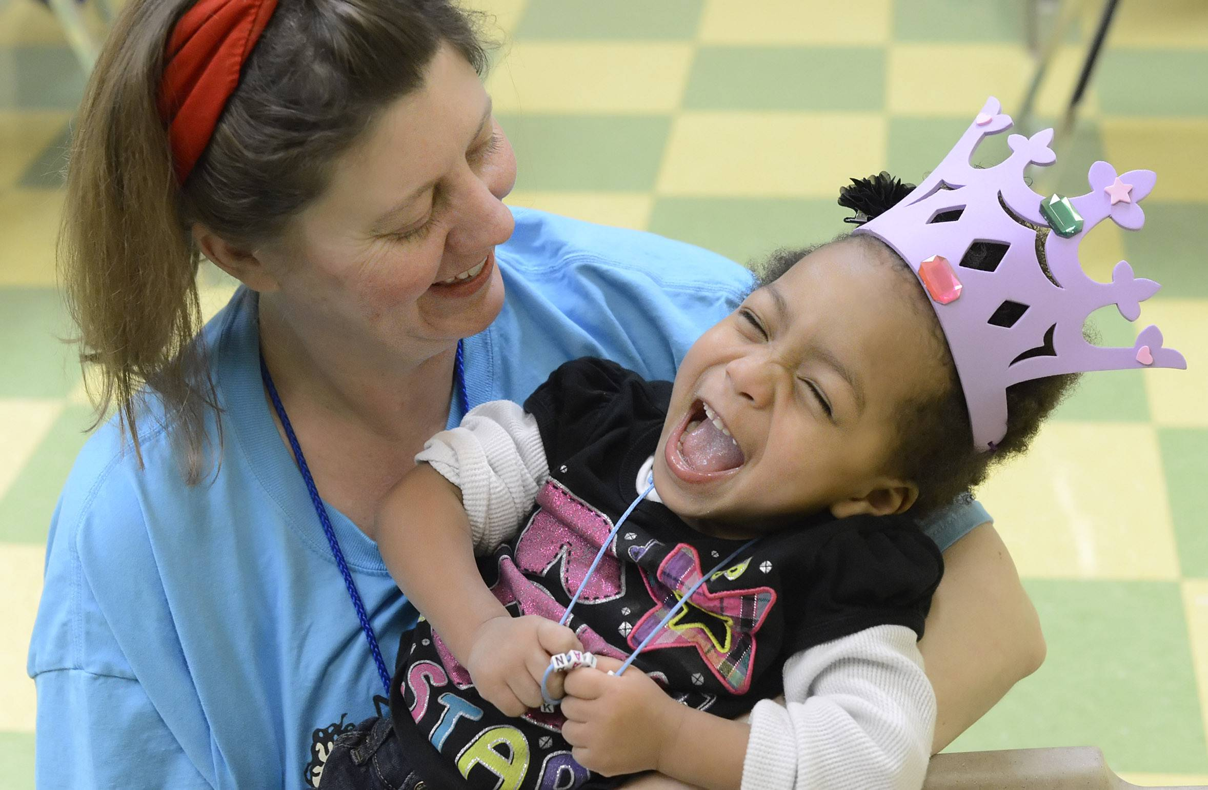 Theresa Hughes of Elburn makes Kei'anna Bateman of Kaneville laugh Saturday during a Nathaniel's Hope Buddy Break program at First Baptist Church in Geneva. Hughes and Rachel Christopherson, 13, of Aurora team up and work with Kei'anna during the program designed to provide a brief break for the families of children with special needs.