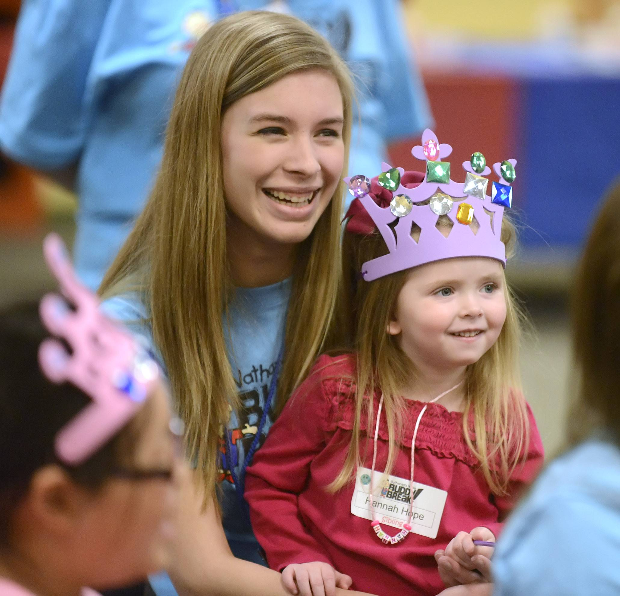 Alena Christopherson, 17, of Aurora holds Hannah Hope, 4, of St. Charles in her lap as they watch a magic show at the second Nathaniel's Hope Buddy Break session held at First Baptist Church in Geneva. The church is one of several in the Chicago area offering the free program that provides respite for families of children with special needs.
